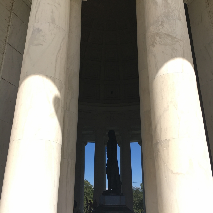 Peering through the columns of the Jefferson Memorial to the bronze statue of one of our founding fathers.