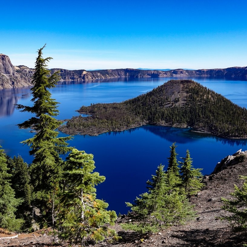 Wizard Island arises from the deep-blue waters of Crater Lake.