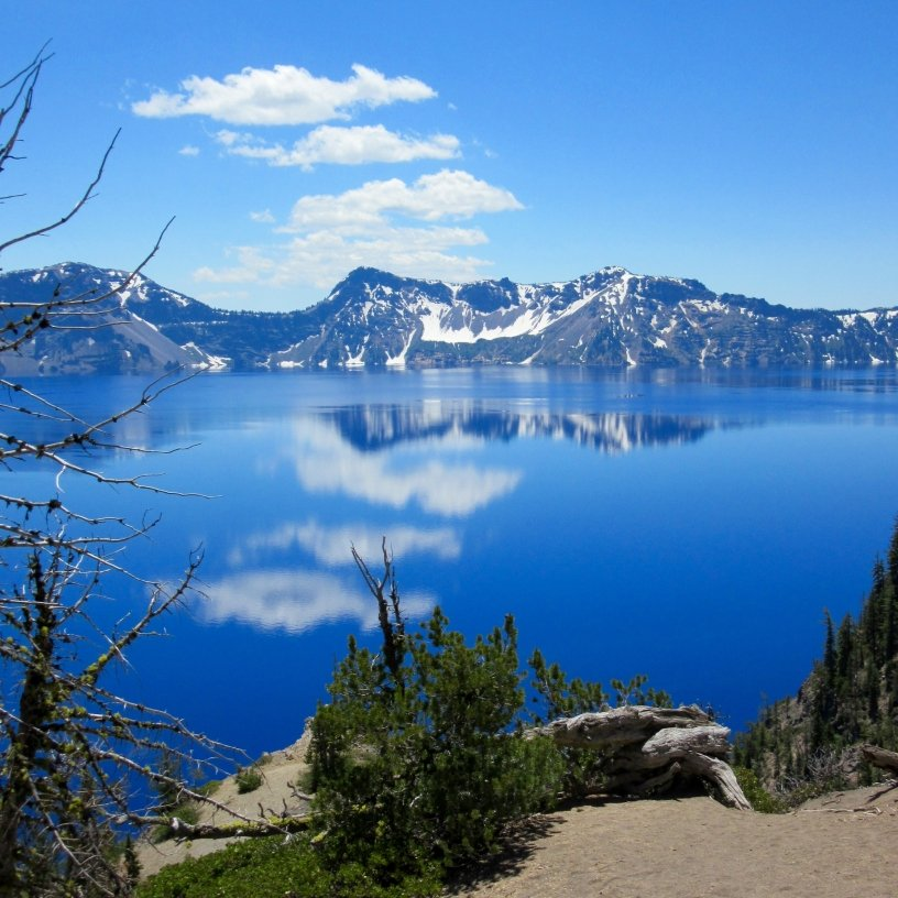 Crater Lake with clouds and the snowy far rim reflected in the water.