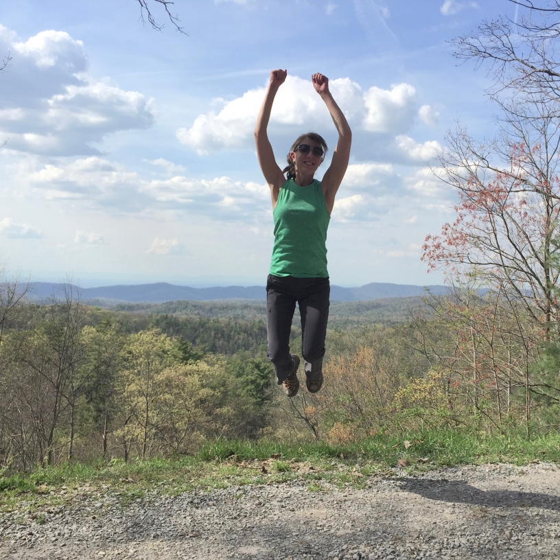 Me jumping high with a background of a beautiful Tennessee mountain range, blue sky and clouds.