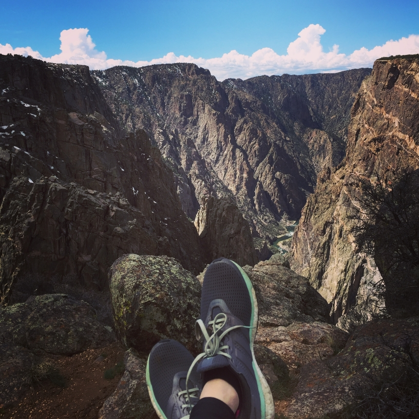 Feet wearing running shoes rest on the edge of a steep, rocky canyon with sun lighting some of the walls and a river far below