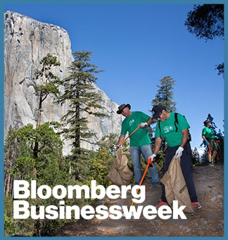 Two volunteers help with a clean-up at Yosemite National Park. On top of the image, the Bloomberg Business logo in white
