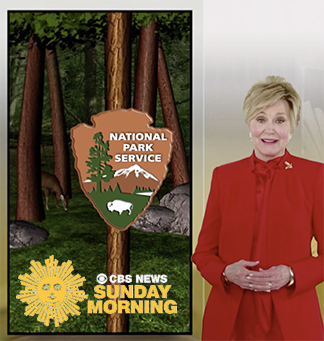Jane Pauley, host of CBS Sunday Morning, stands in front of a screen displaying an image from the Redwood National and State Parks, as well as the National Park Service logo