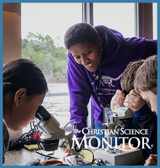 A teacher leans over to assist a group of students huddled around a microscope