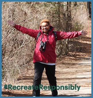 LaTresse Snead stretches her arms out on a walk in a park, wearing binoculars. On top of the image is the logo for #RecreateResponsibly in green. The entire image is framed by a light blue box.