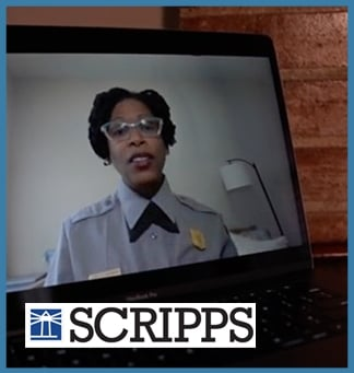 A laptop displays a recording of a person talking in NPS uniform. On top of this image is the Scripps logo. The entire image is framed by a light blue box.