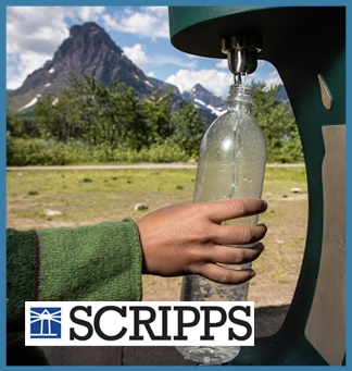 A hand reaches out to refill a waterbottle at a bottle refill station in a park. Over this image is the Scripps logo. The entire image is framed in a light blue box.