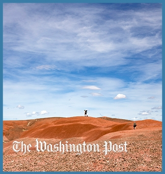 Tiny hikers on the red badlands with a blue sky with some clouds