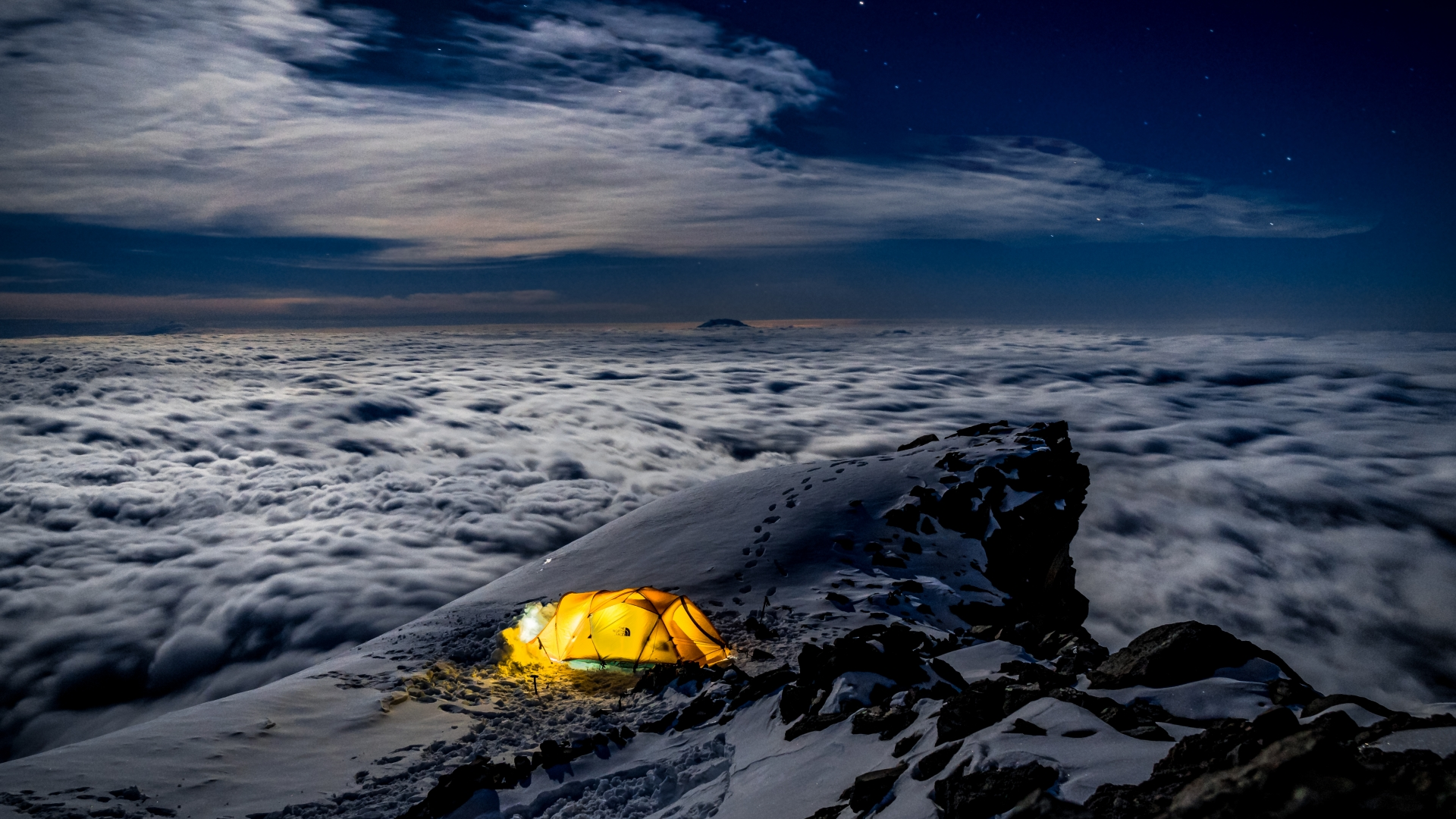 A tent with a light on a mountaintop above the clouds