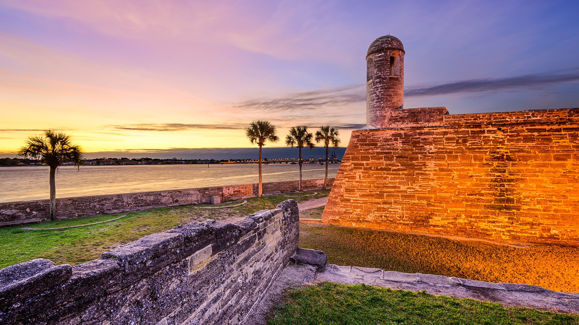 Castillo de San Marcos National Monument at sunsest with water and palm trees in the background