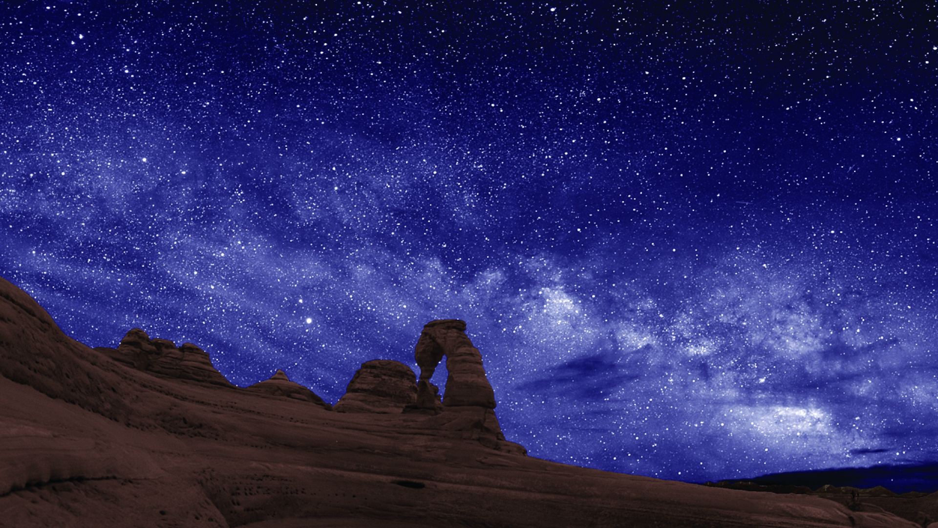 The white milky way in the purple-blue sky over Delicate Arch at Arches National Park