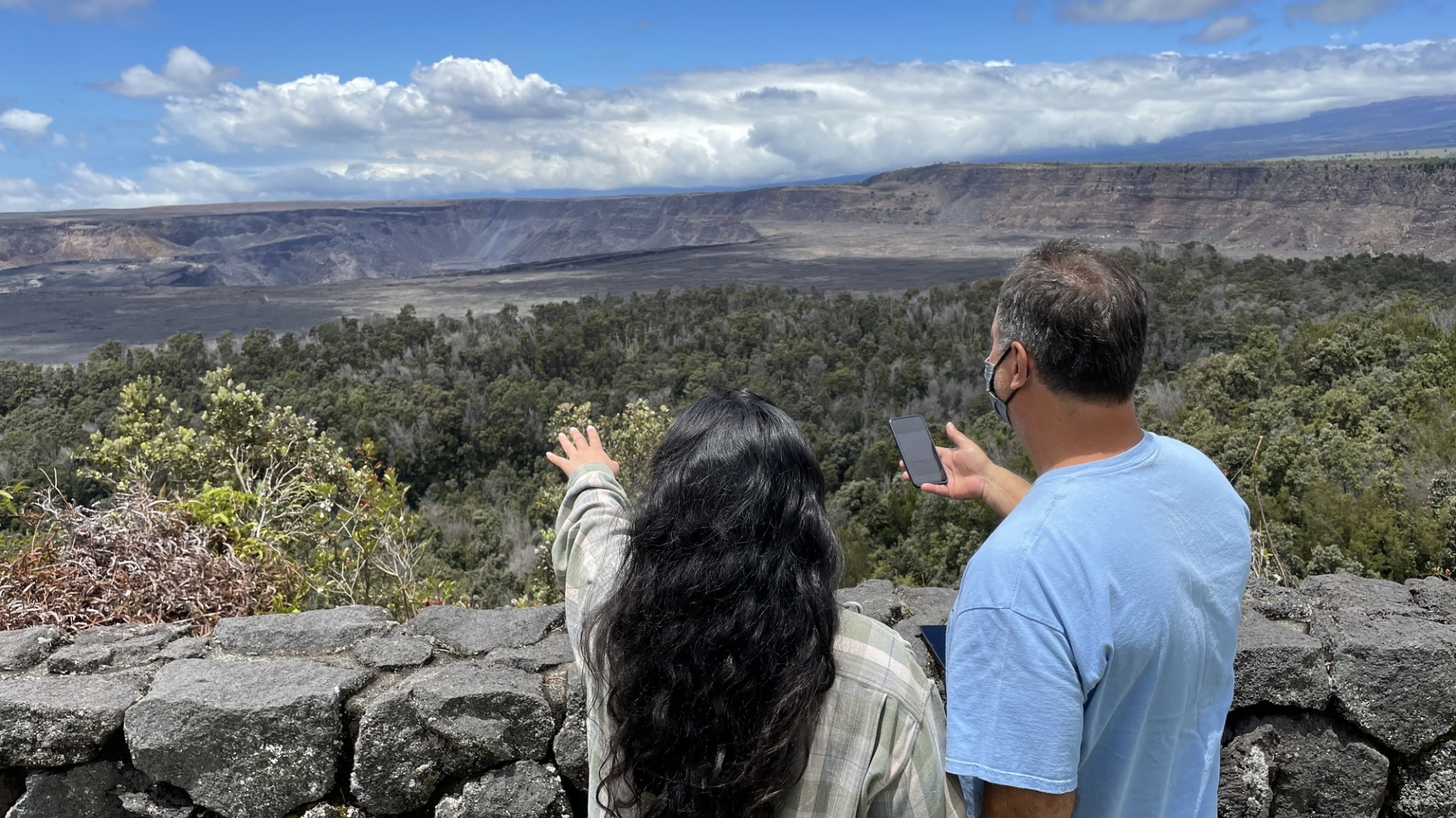Two visitors standing at an overlook pointing towards a volcanic crater