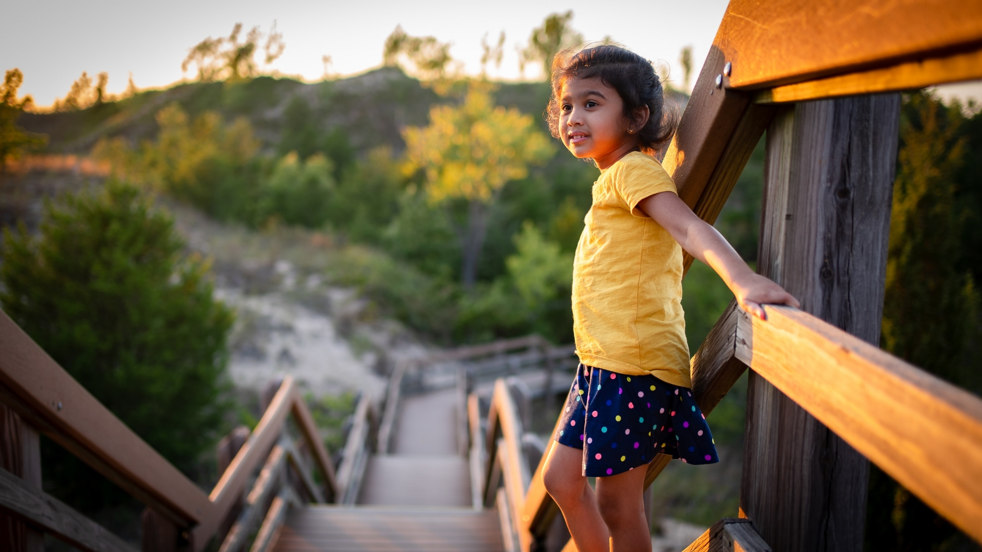 A young girl holds onto a wood pathway's guide rail and looks out onto a sunset scene