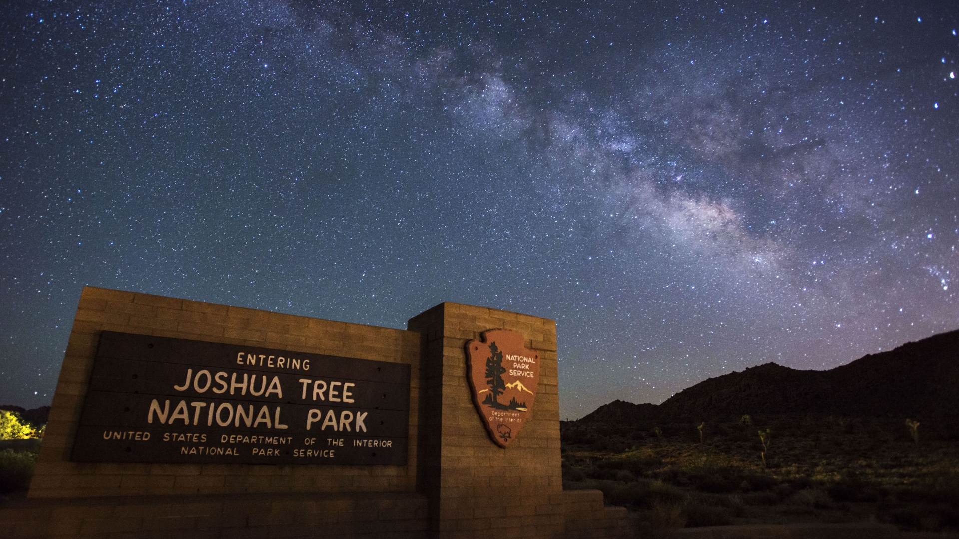 The Milky Way in the starry night sky with the Joshua Tree National Park entrance sign in the foreground