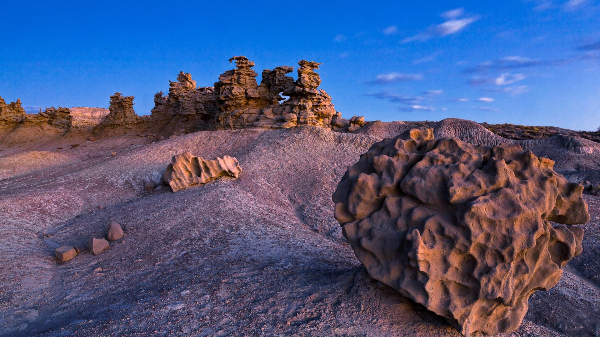 Alien-like dimpled rock in the foreground of more funky formations under a blue sky at Fantasy Canyon