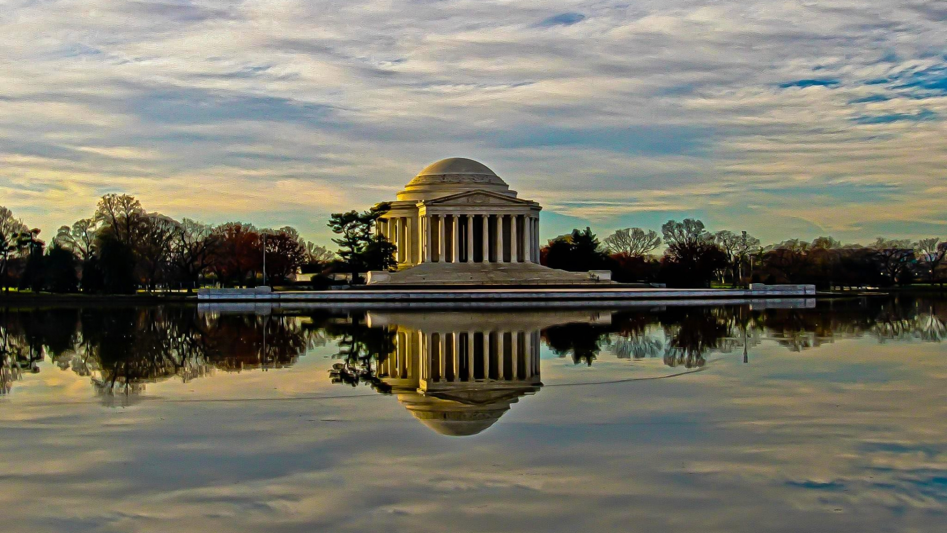 A waterfront view reflects the grandeur of the Thomas Jefferson Memorial as fall trees border each side and a sunset sky filled with clouds hovers above.