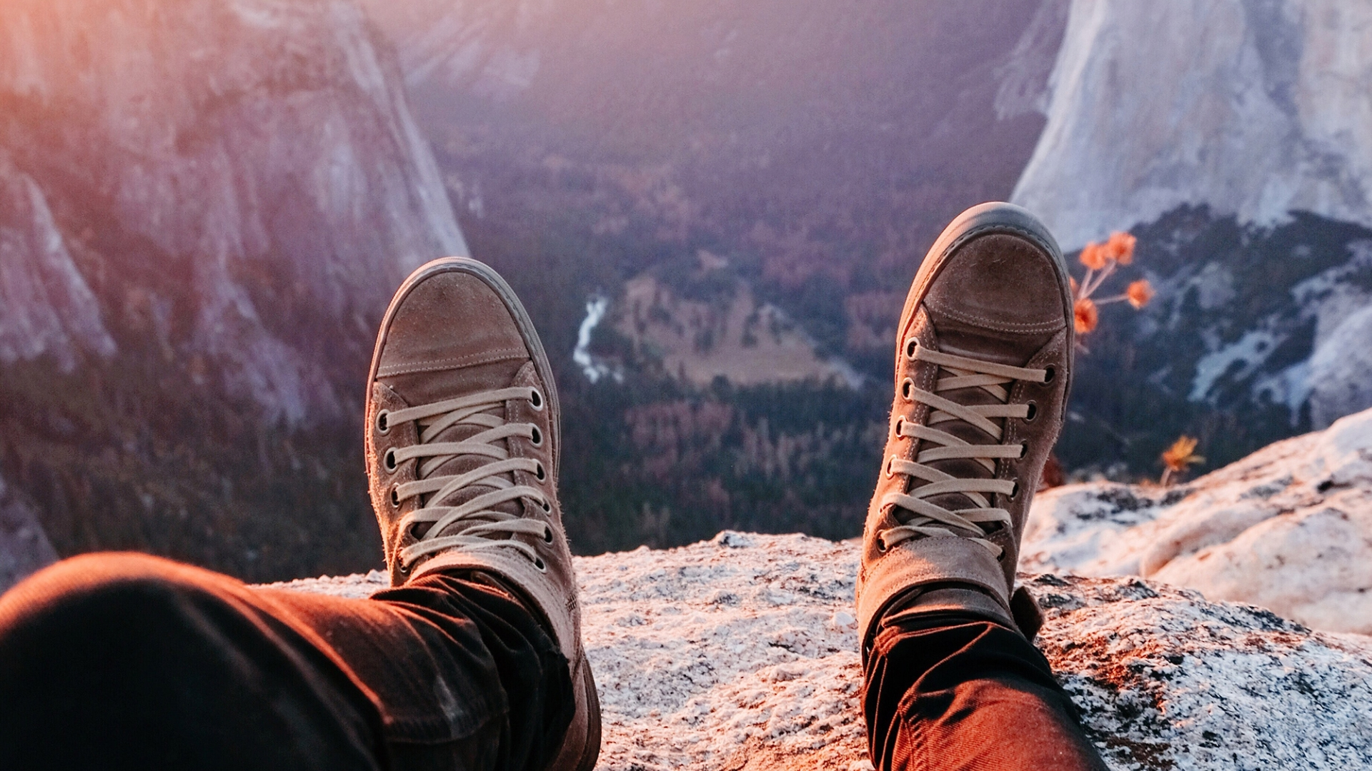 Seen from the legs down, we see legs and a pair of boots resting on a grey stone cliff.