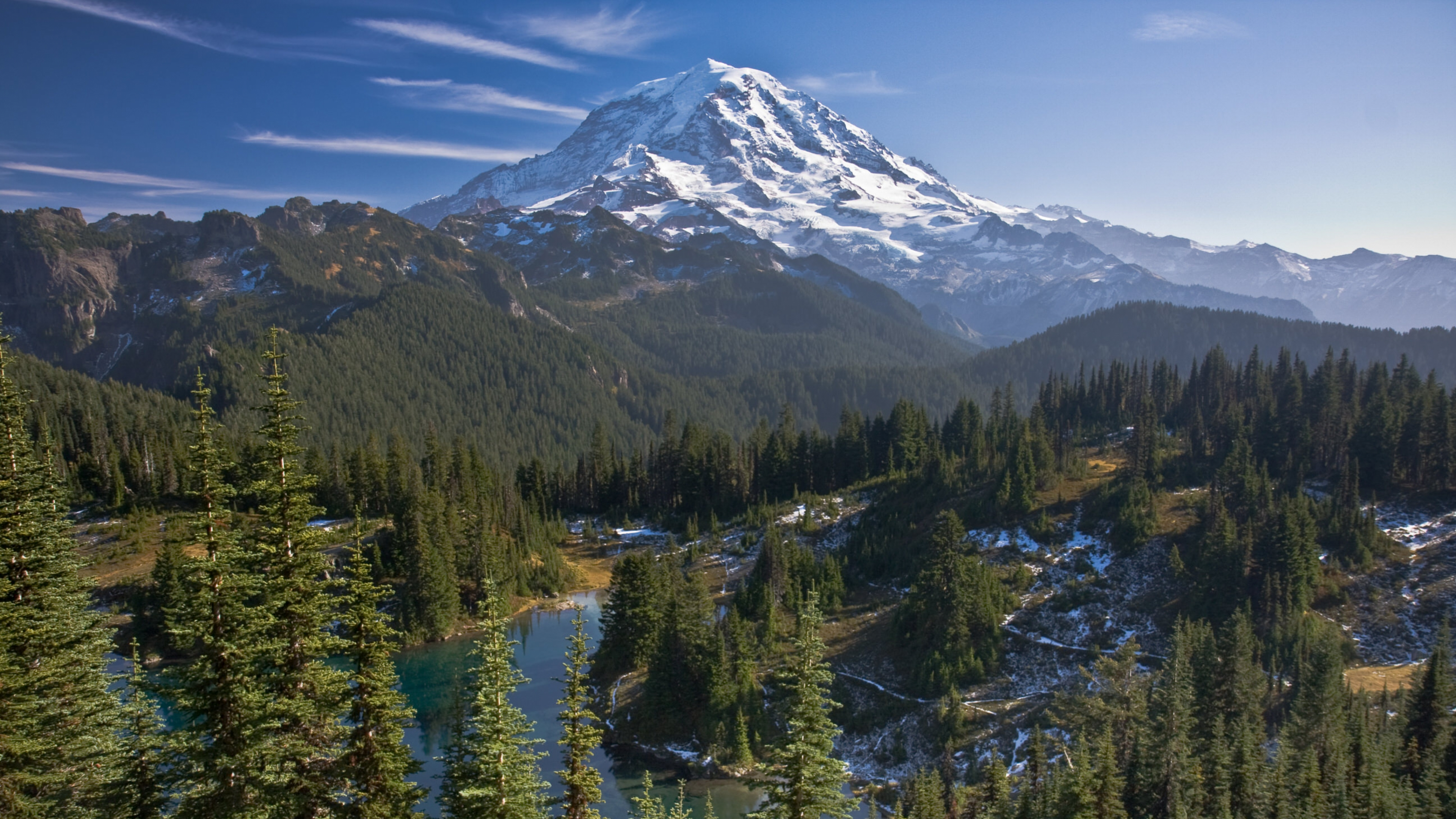 Snow-covered Mount Rainier behind evergreens and a river