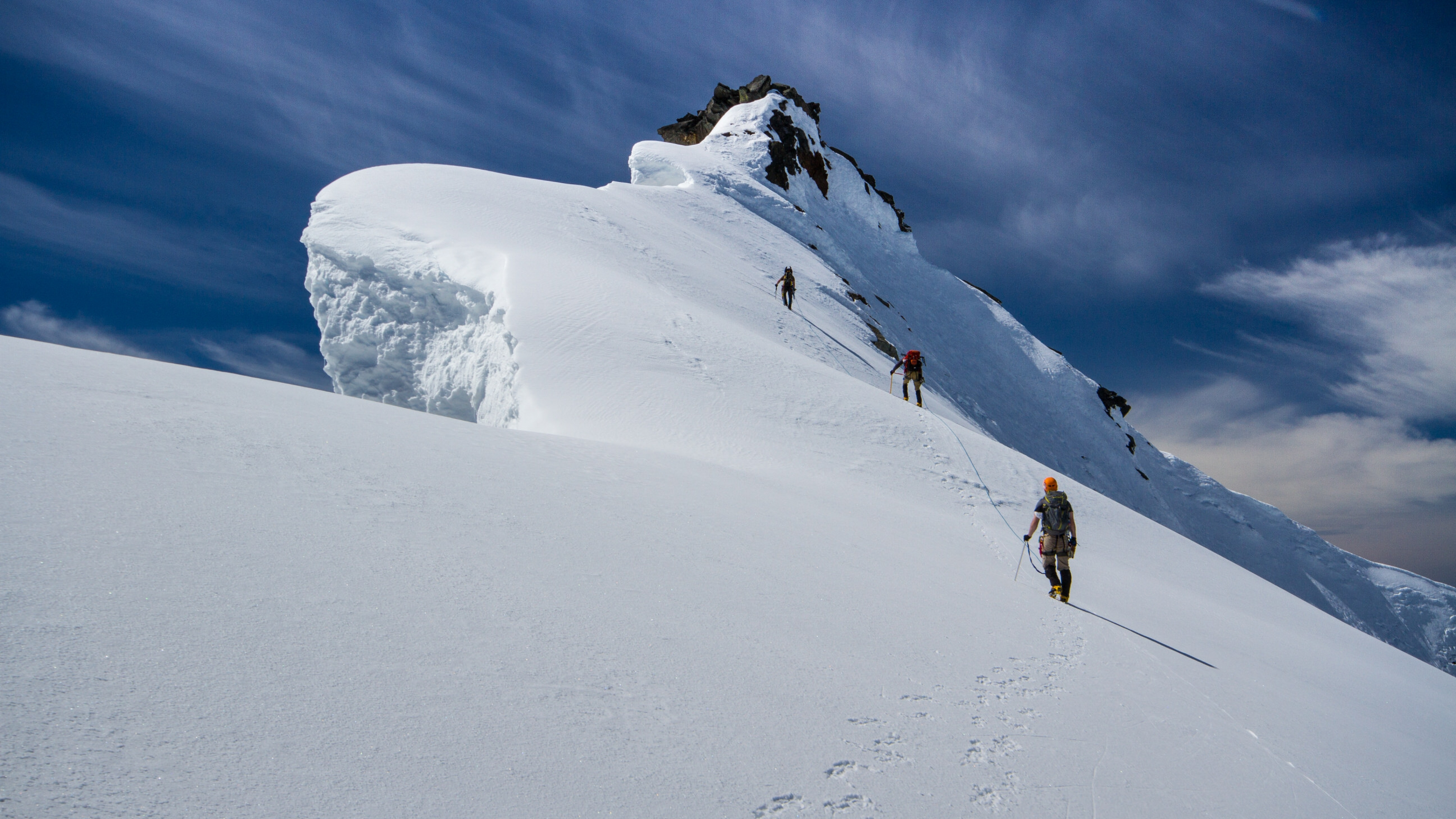 Roped mountaineering team near the top of Sahale Peak at North Cascades National Park