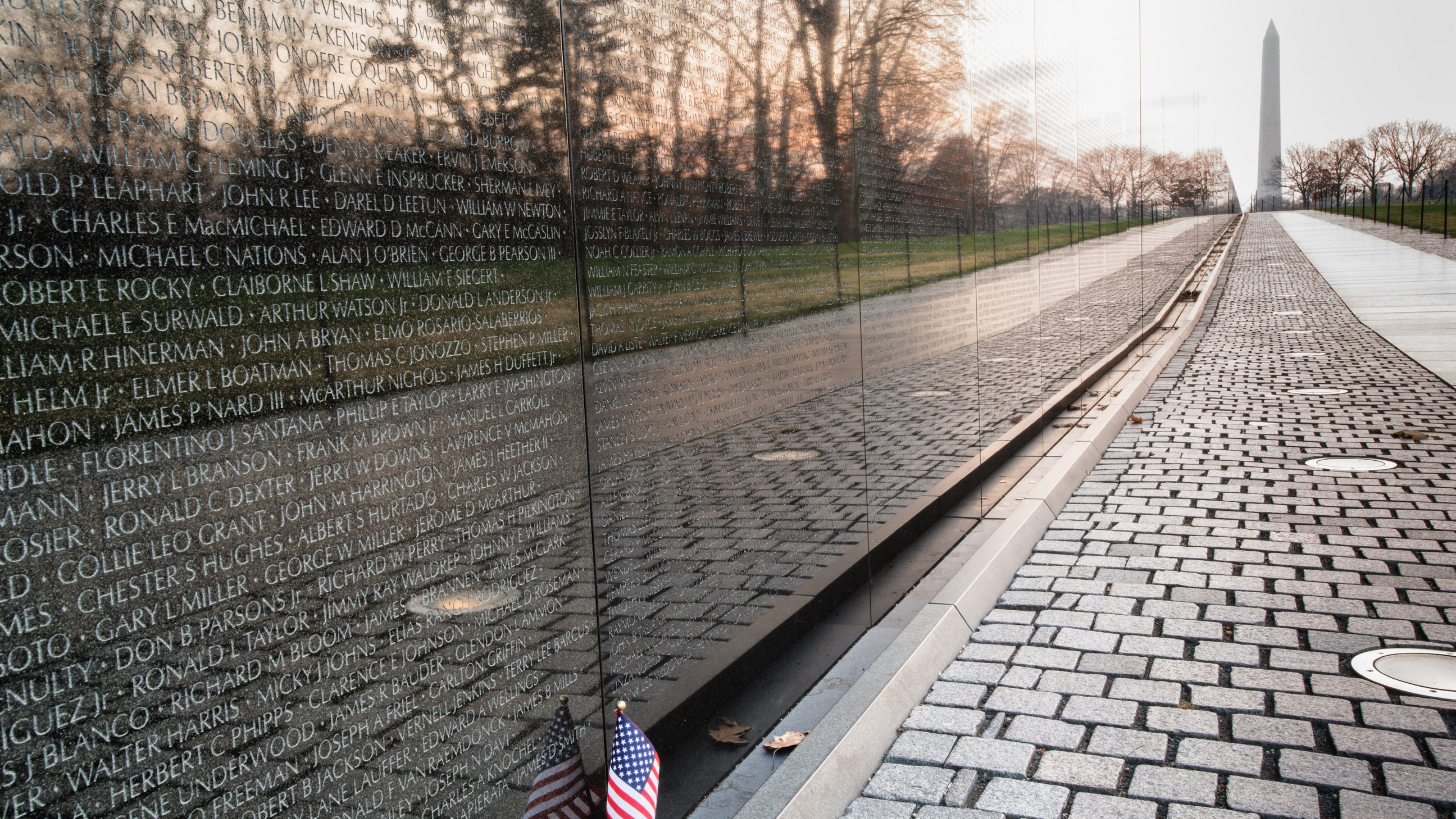 Small American flag against the Vietnam Memorial with the Washington Memorial in the background