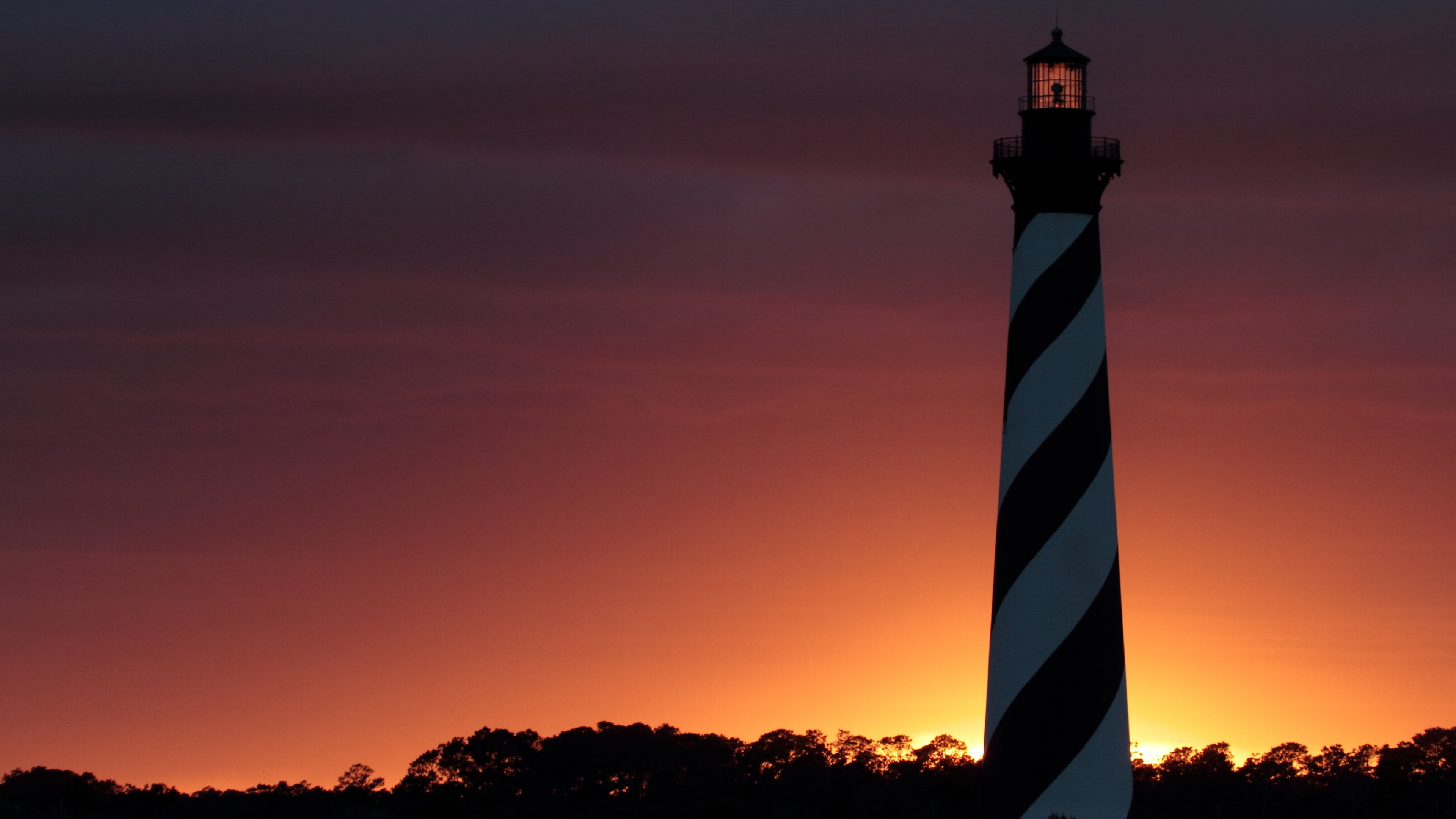 Sun setting behind striped lighthouse tower at Cape Hatteras National Seashore
