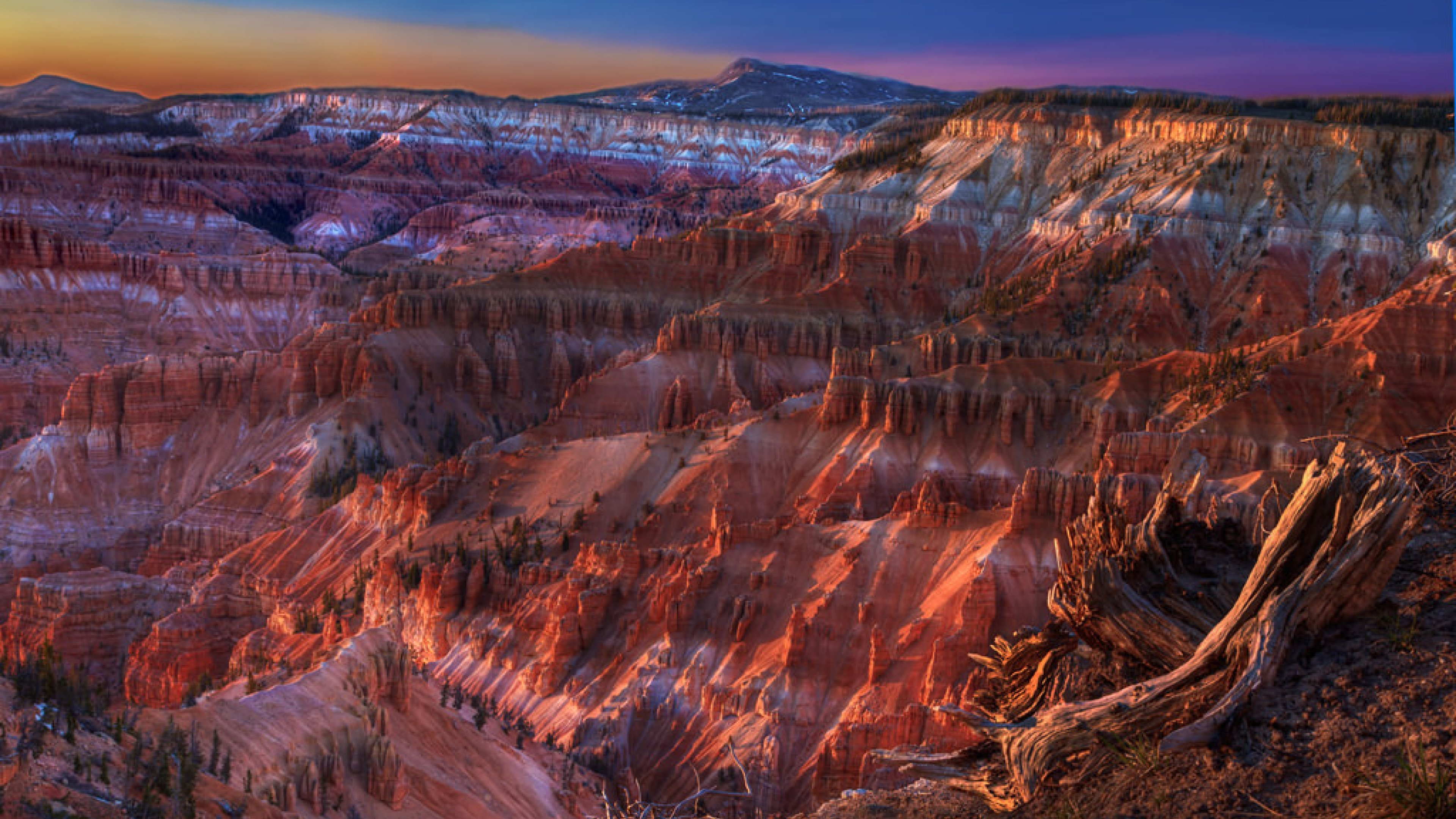 Colorful suset illuminating white, red, and purple sandstone cliffs of Cedar Breaks National Monument