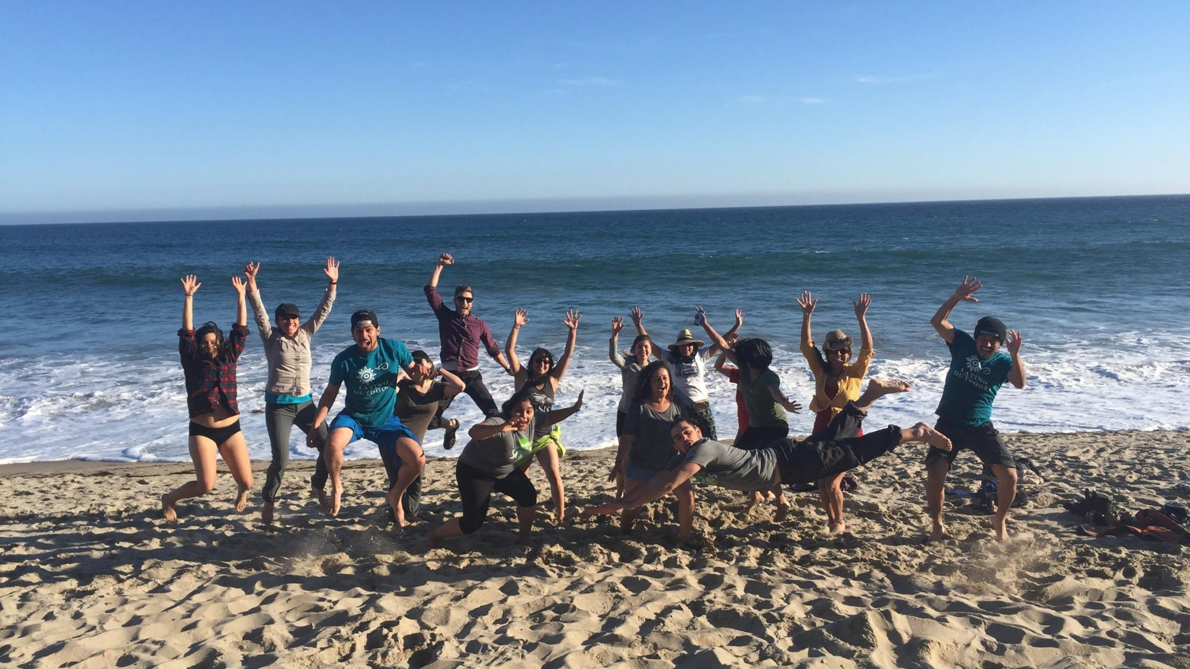 Group of Latino Outdoors staff jumping on a beach