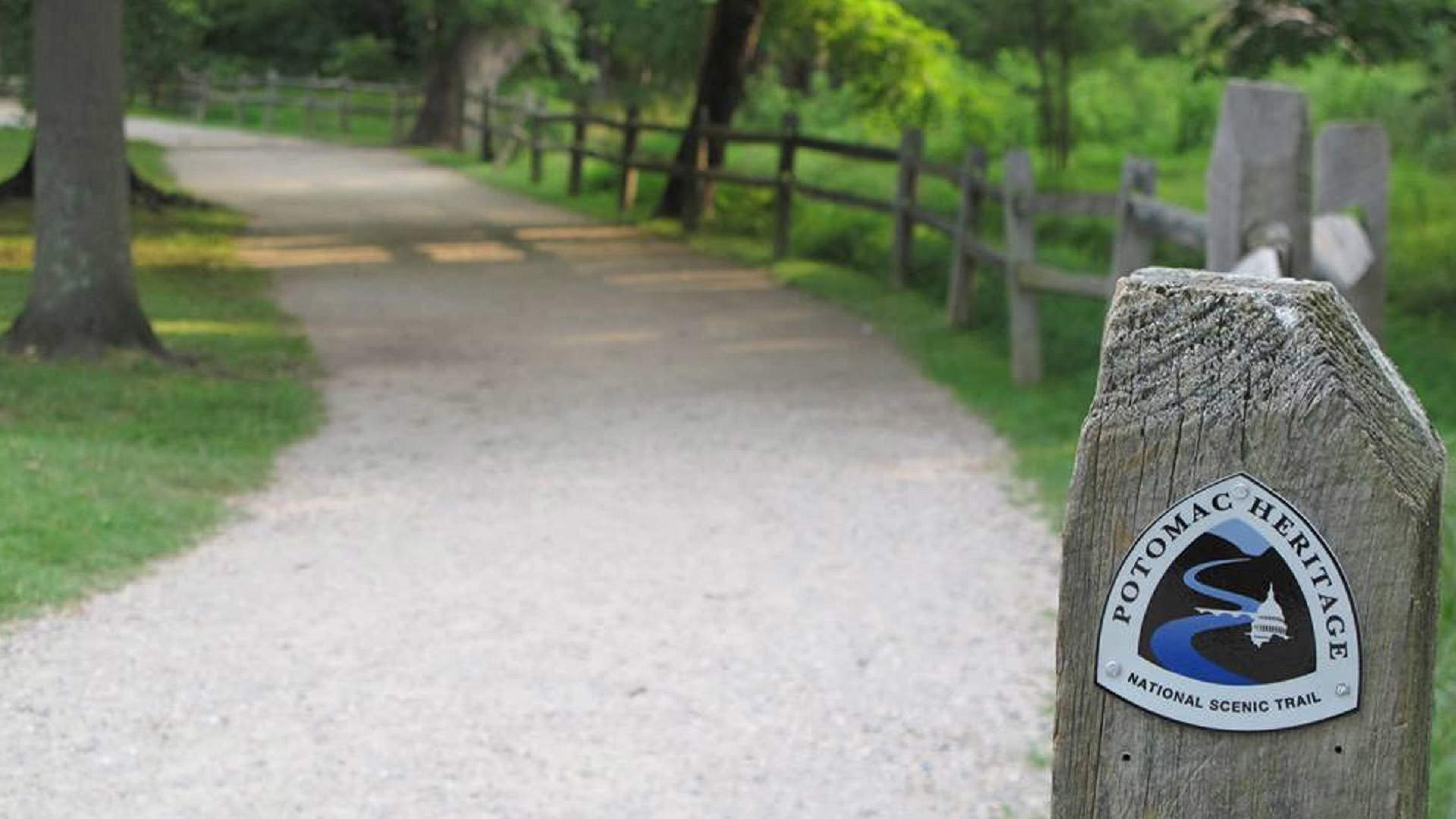 Signpost marks the start of gravel trail along rustic fence and trees