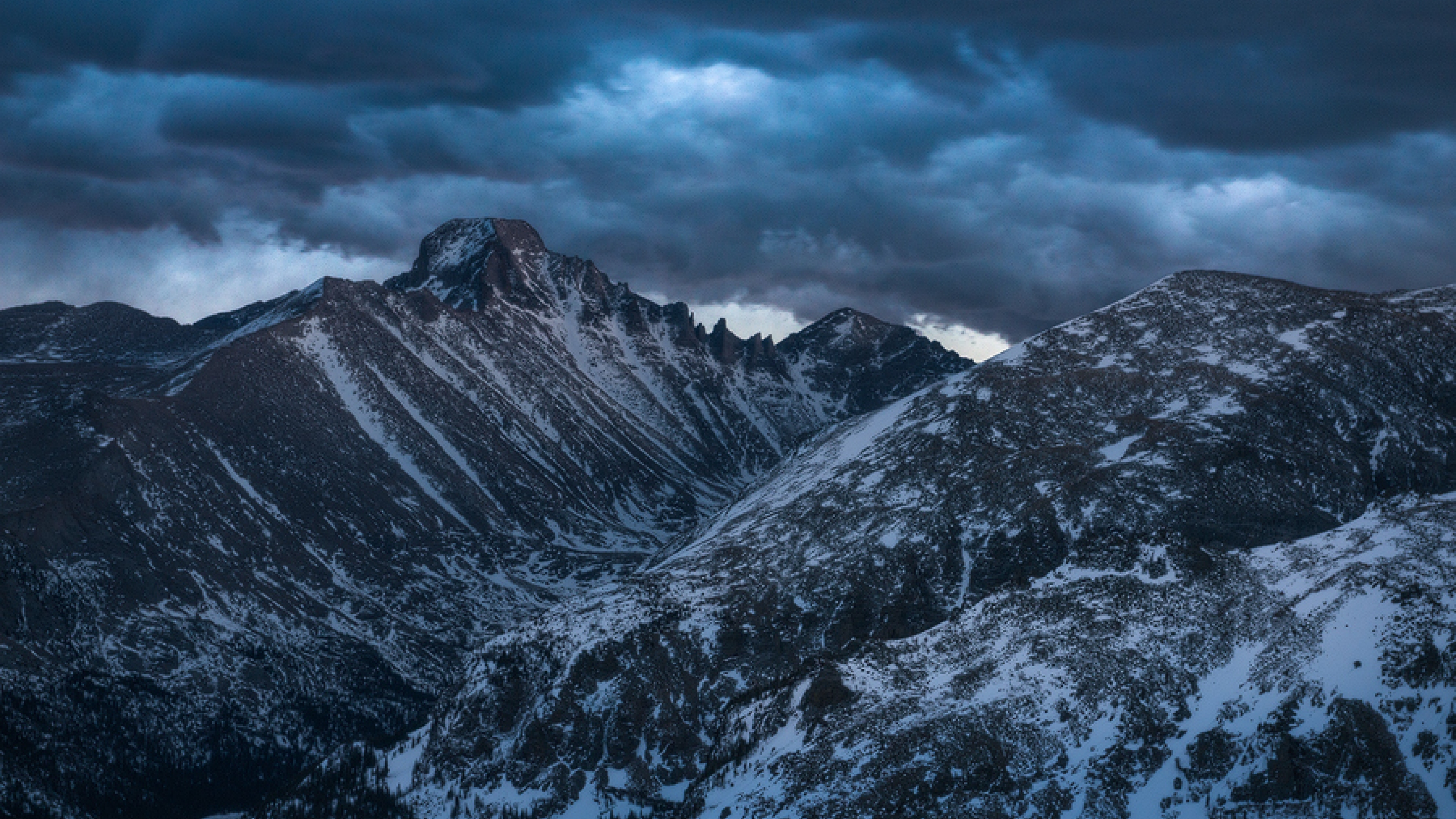 Ominous photo of Rocky Mountains in winter with snow and a dark, blue night sky