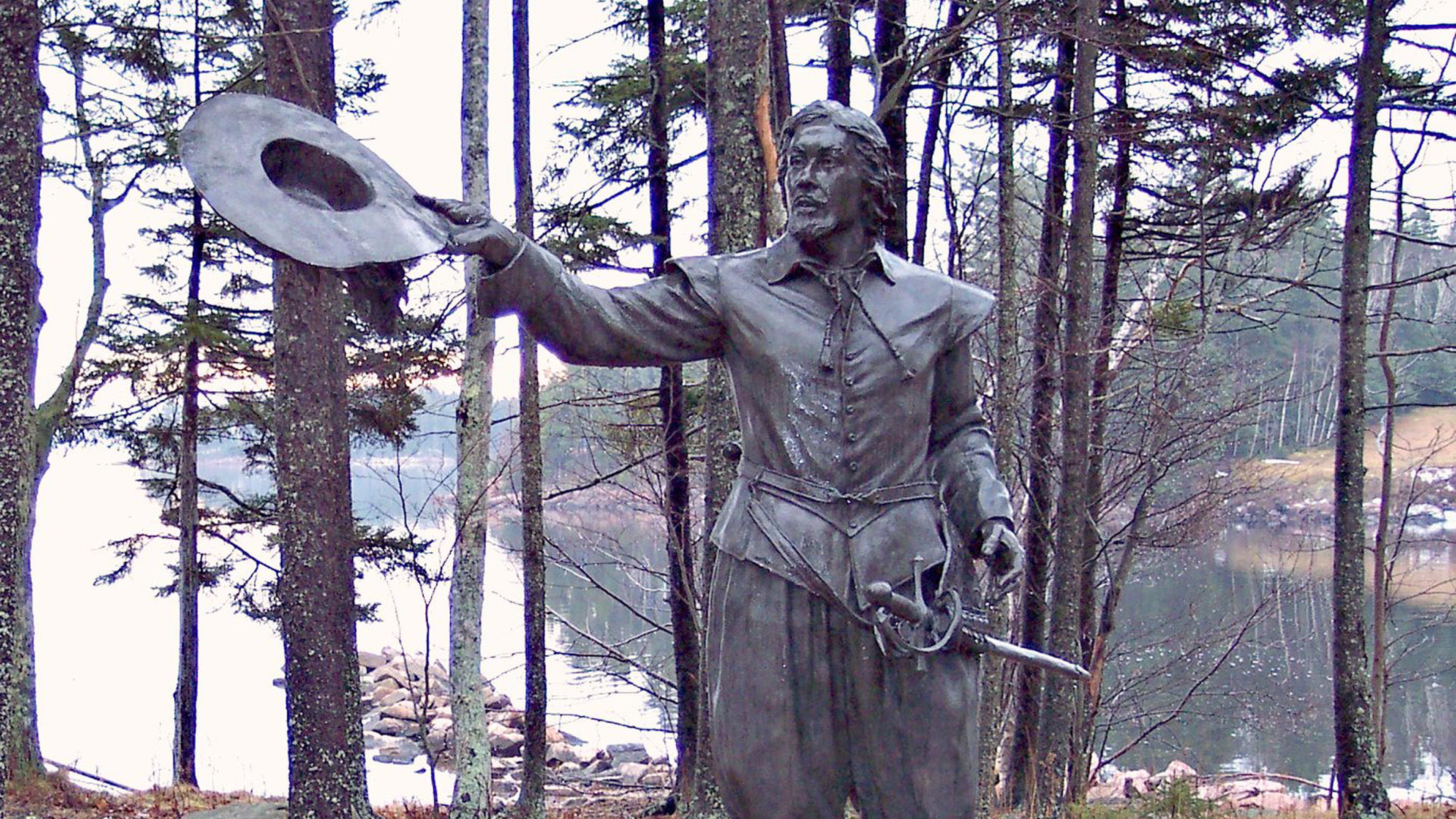 Monument of a man tipping his hat and wearing a sword