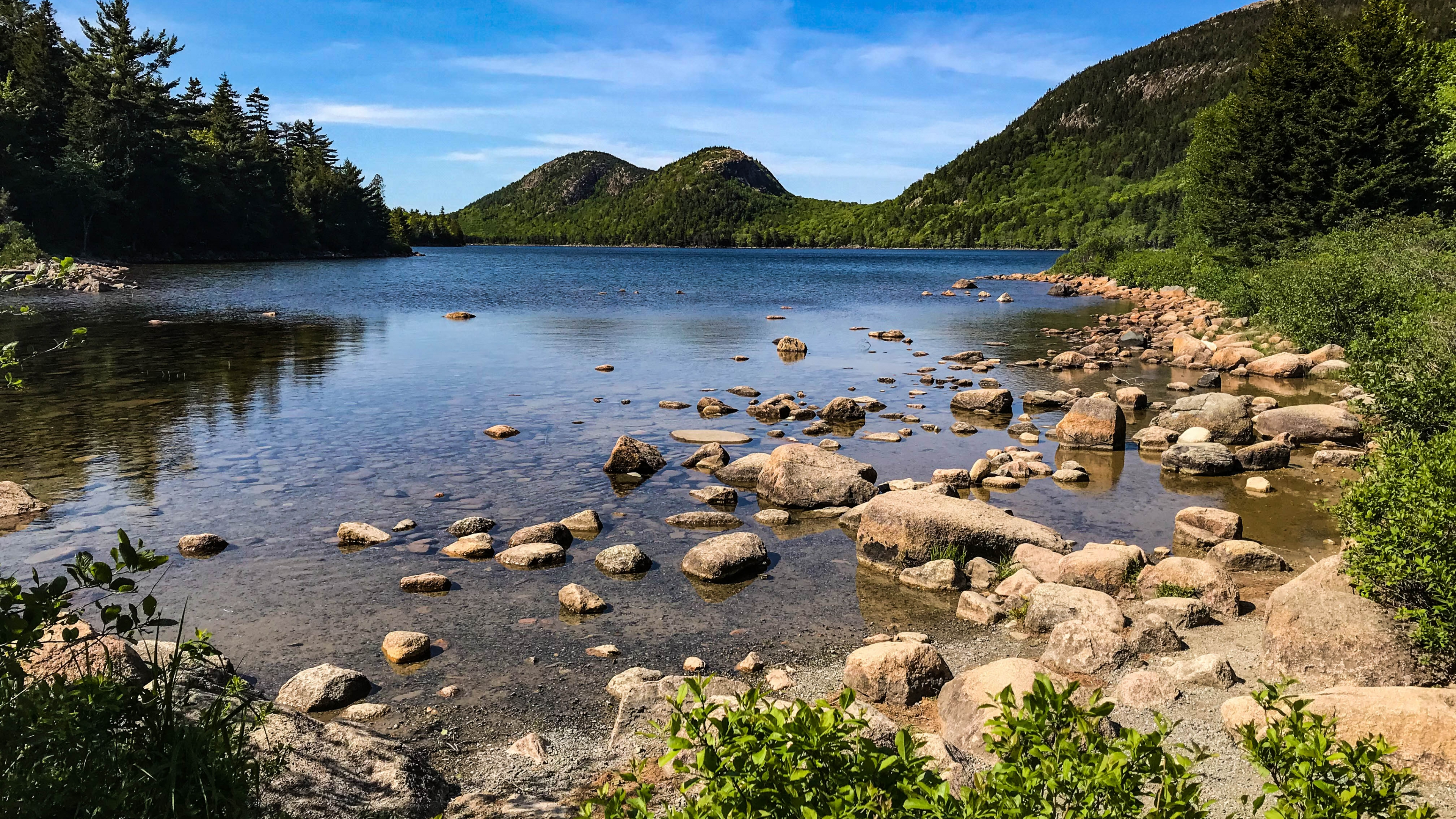 Rocky shoreline around a calm pond. In the distance, rolling green mountains