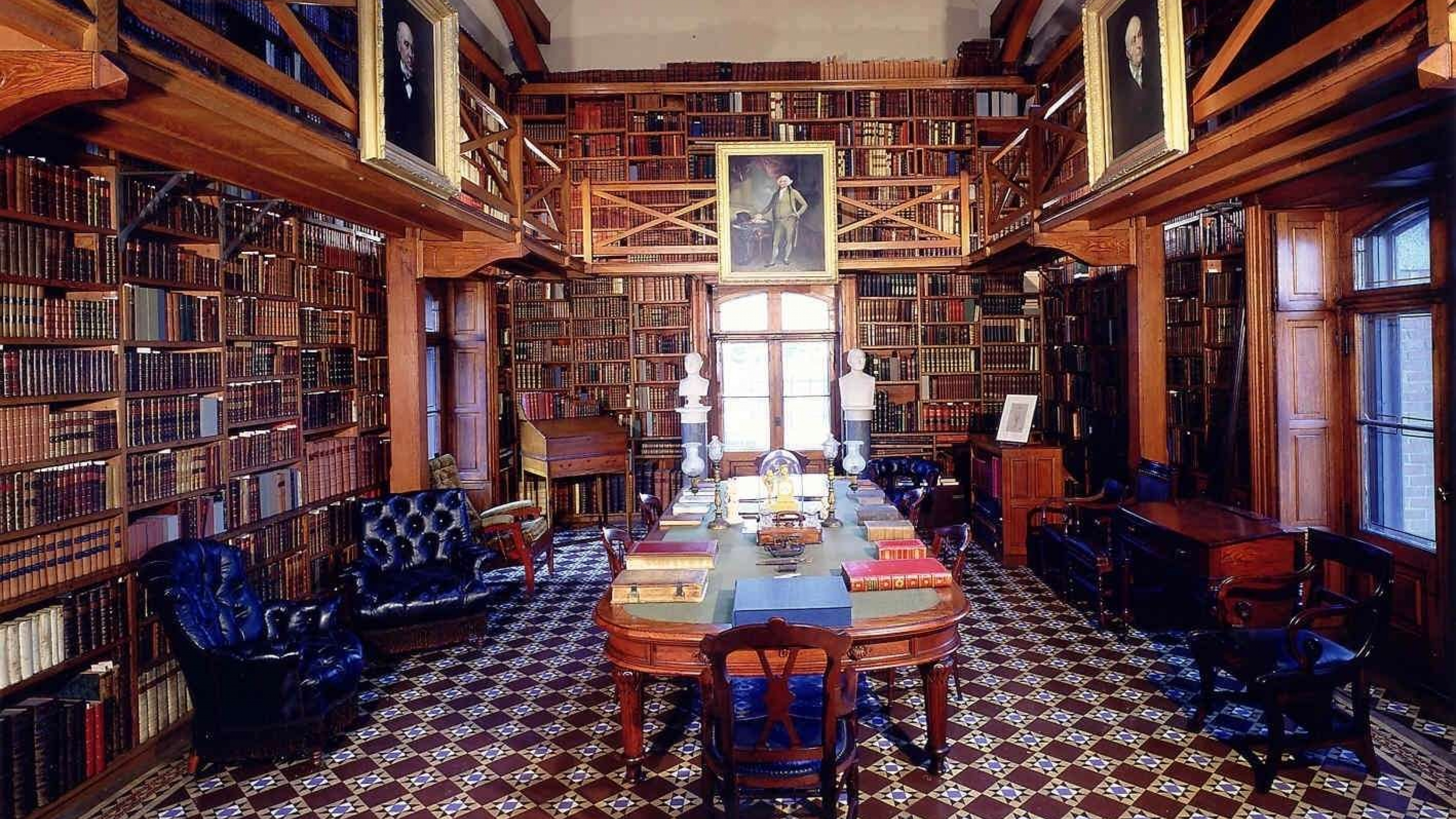 Wooden library with walls of books and an oval table in the center in the Stone Library at Adams National Historical Park