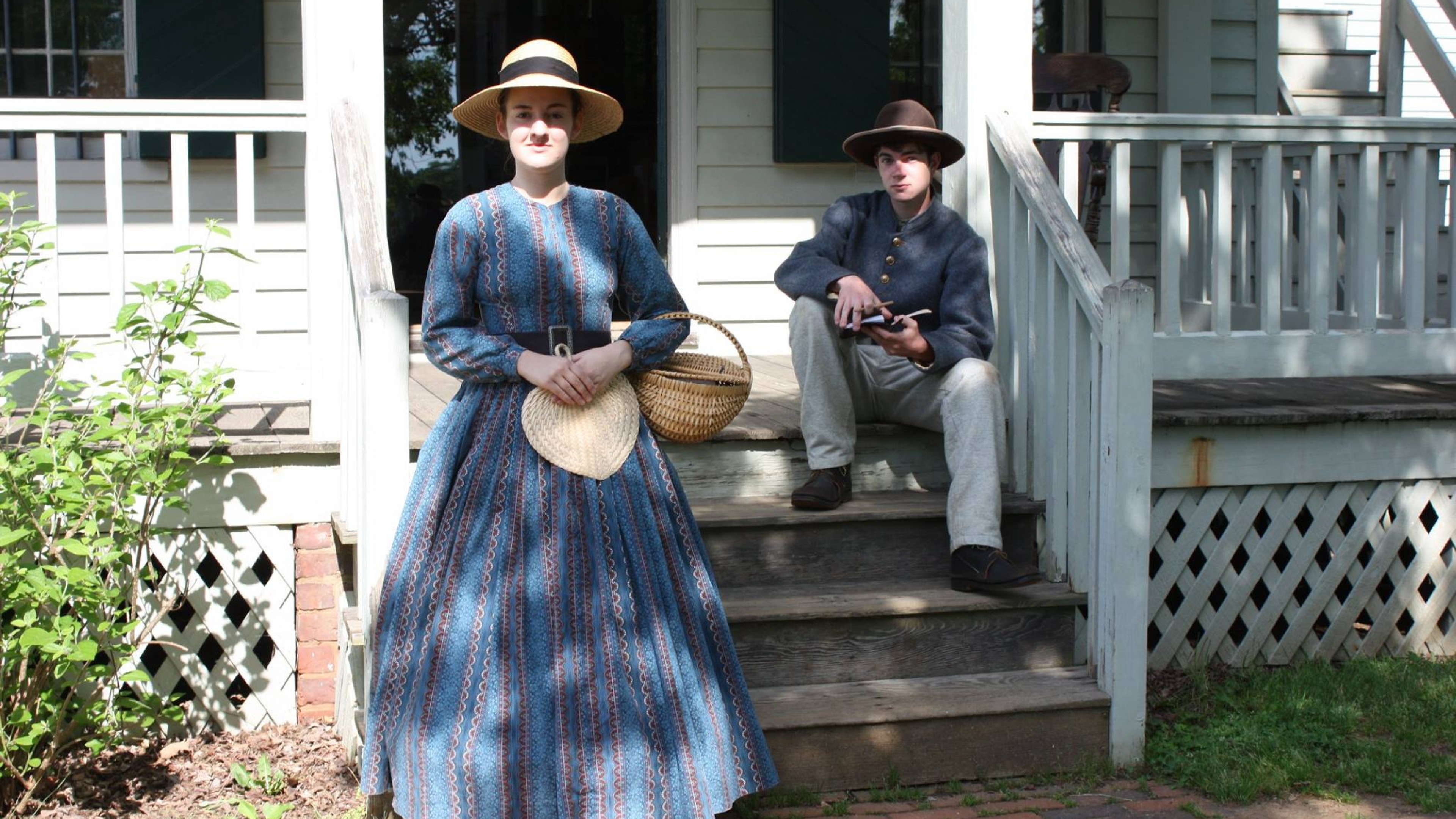 A woman an a boy wearing historical clothes in front of a house at Appomattox Court House National Historical Park