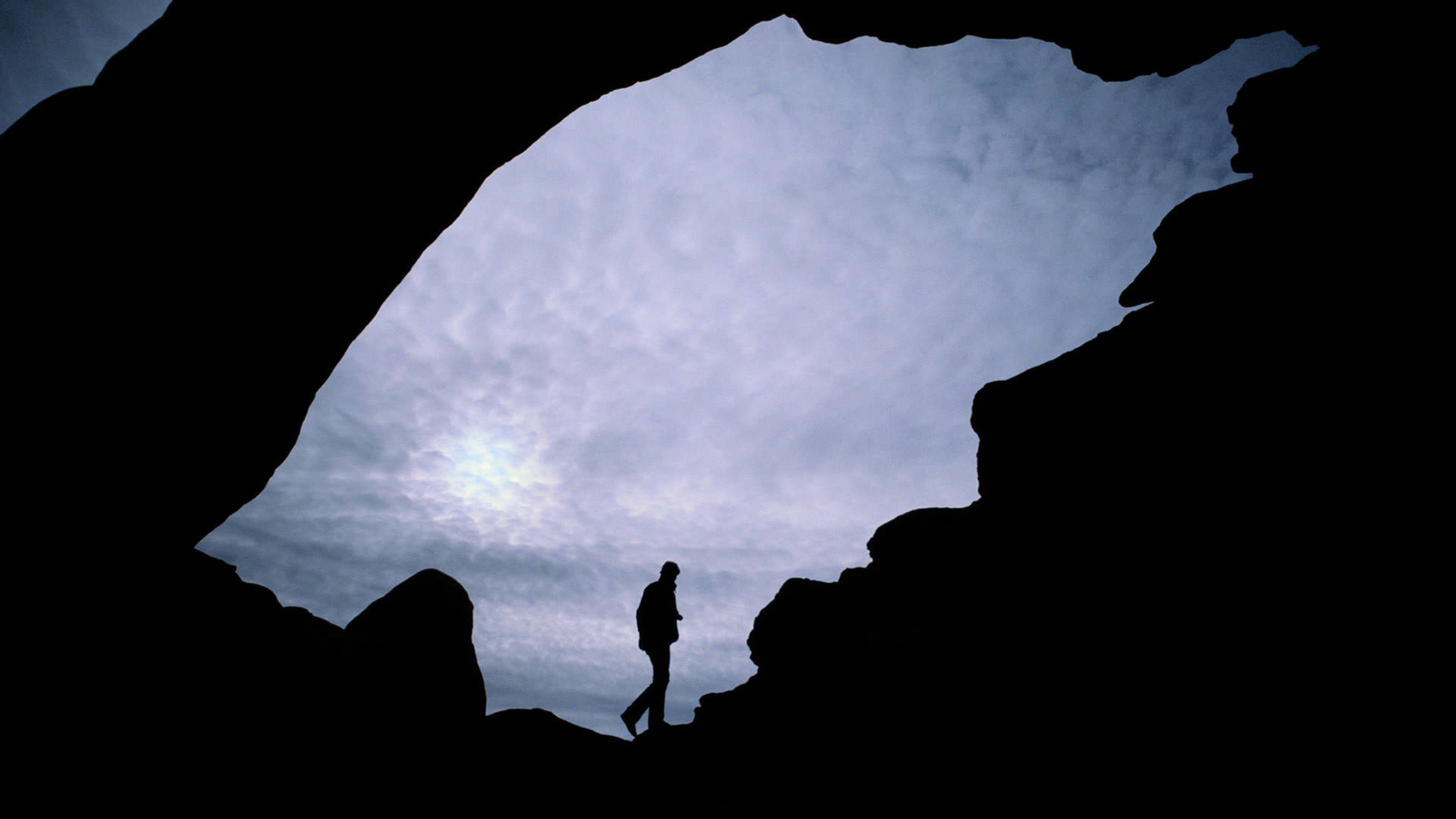 A man in silhouette behind an arch at Arches National Park