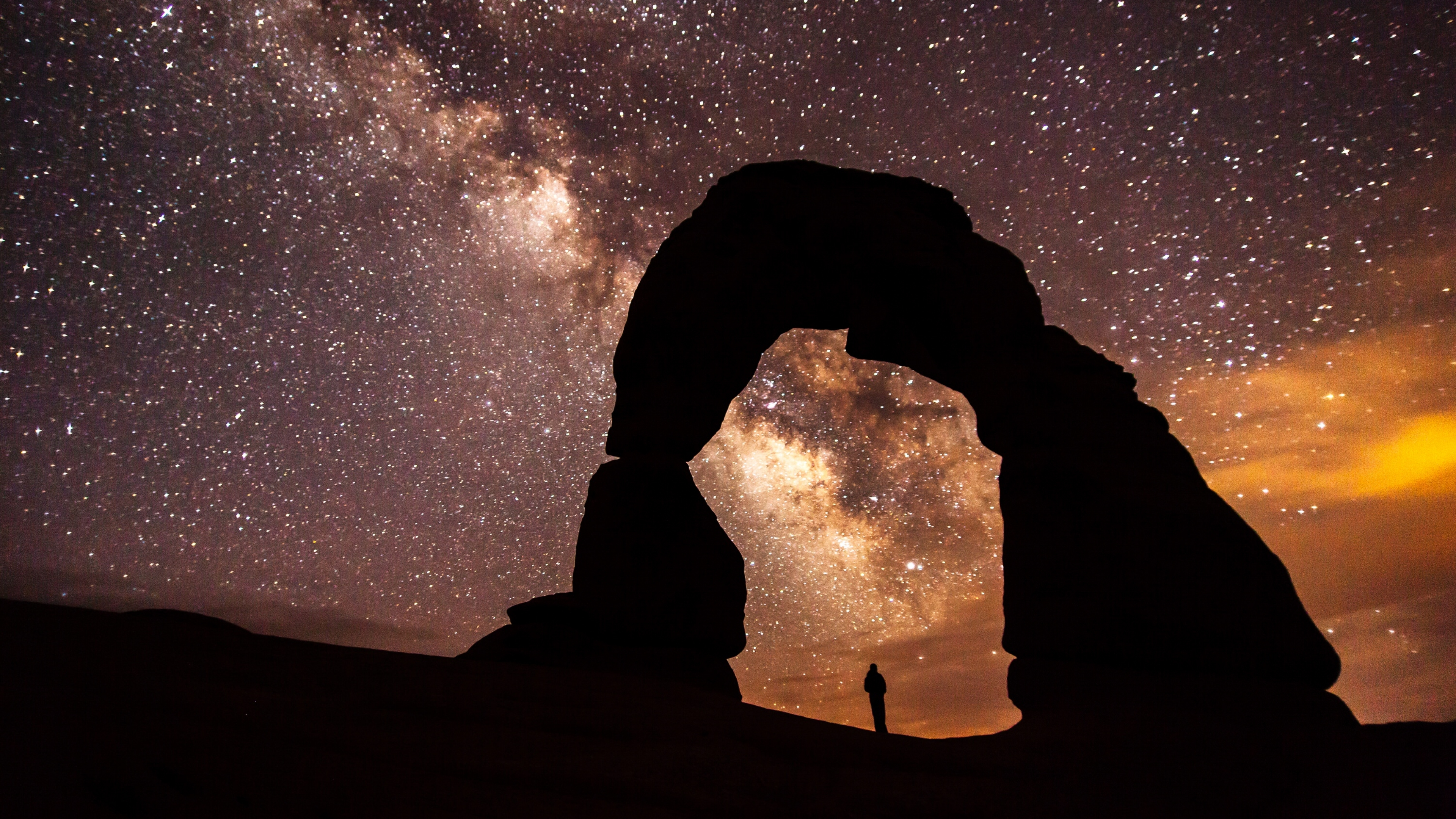 Orange and purple-hued Milky Way with a small person underneath the silhouette of a stone arch at Arches National Park
