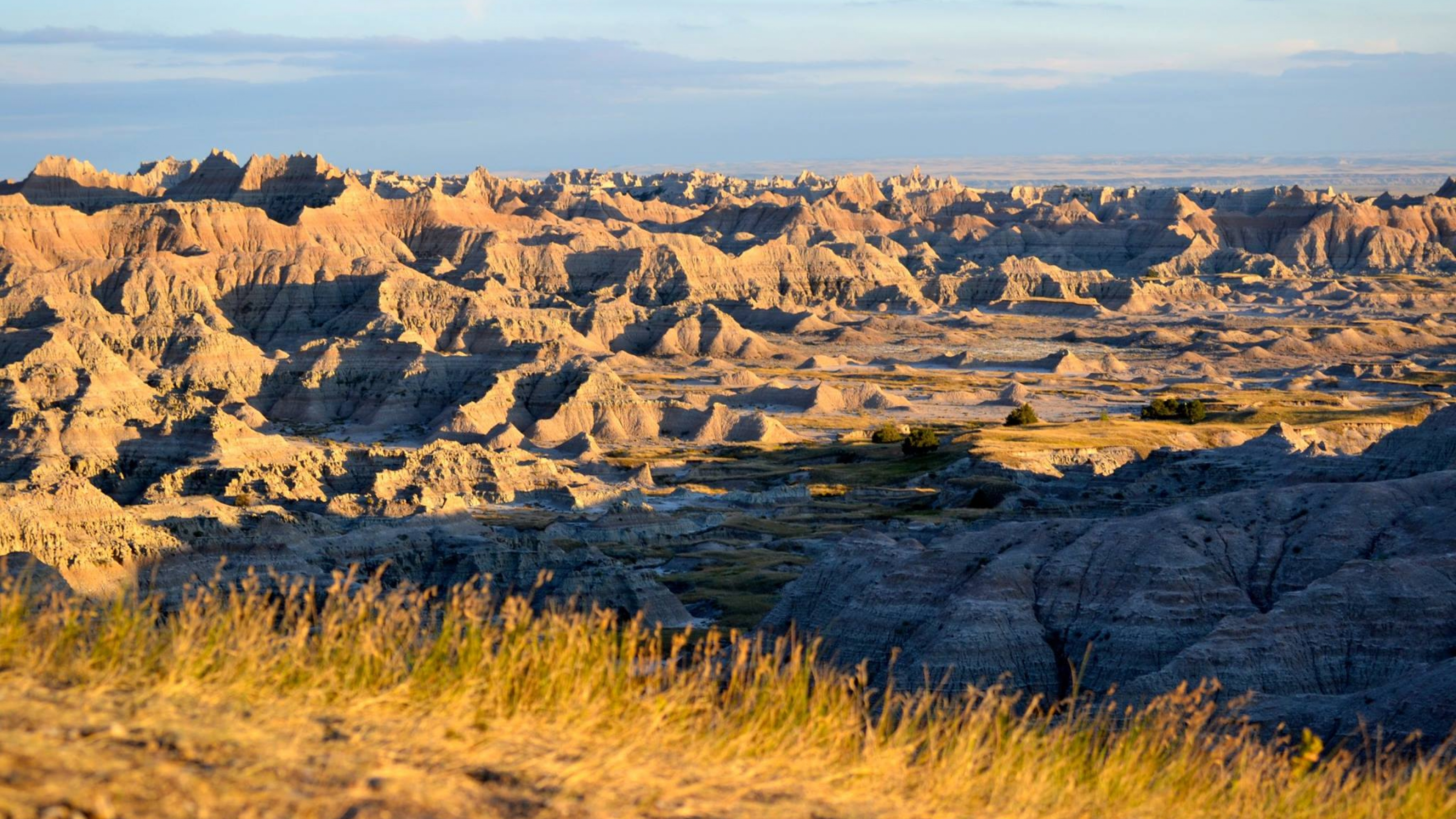 Golden sunlight hitting the sandstone cliffs and hills of Badlands National Park
