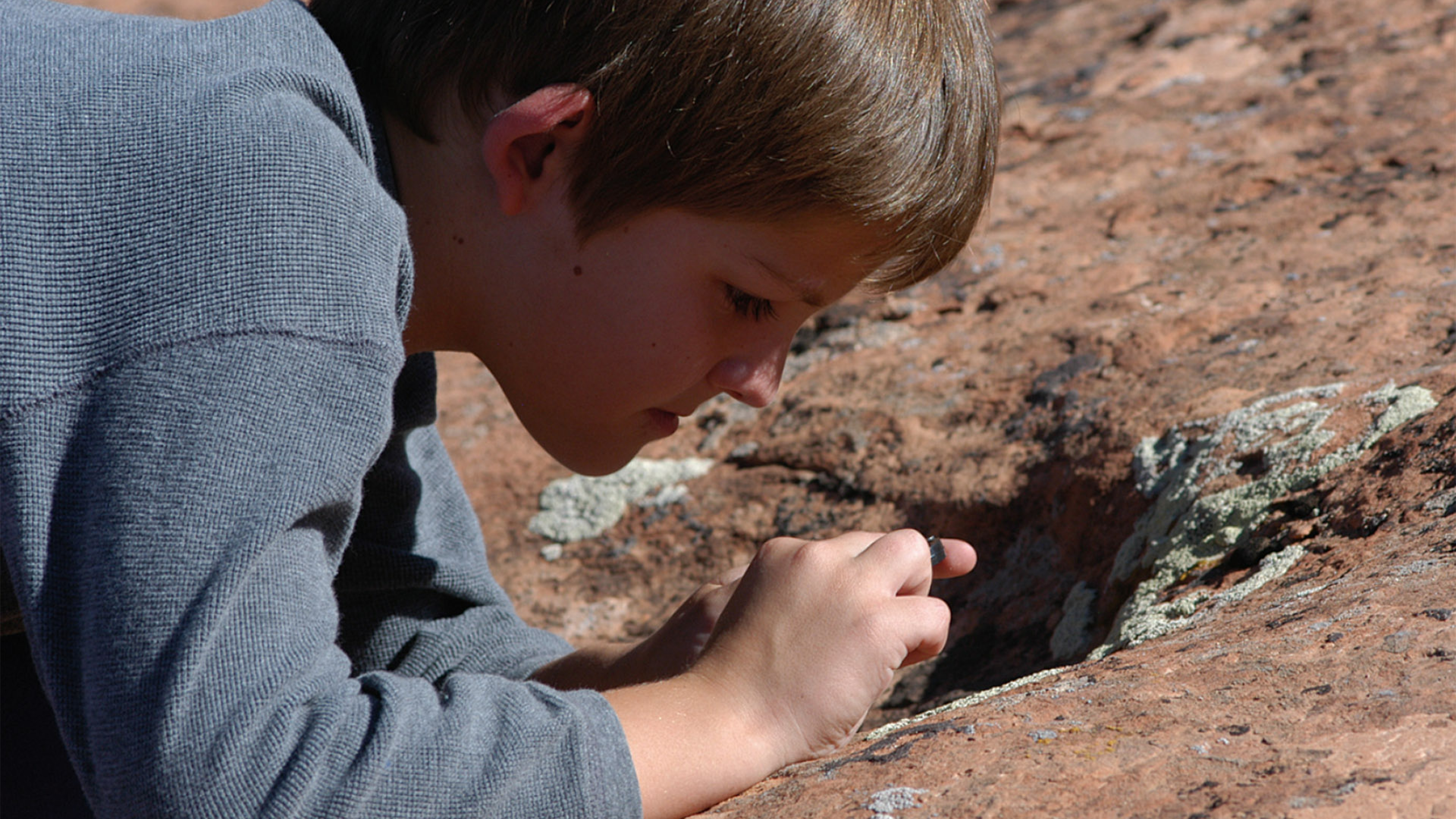 Boy studying lichens in Arches National Park