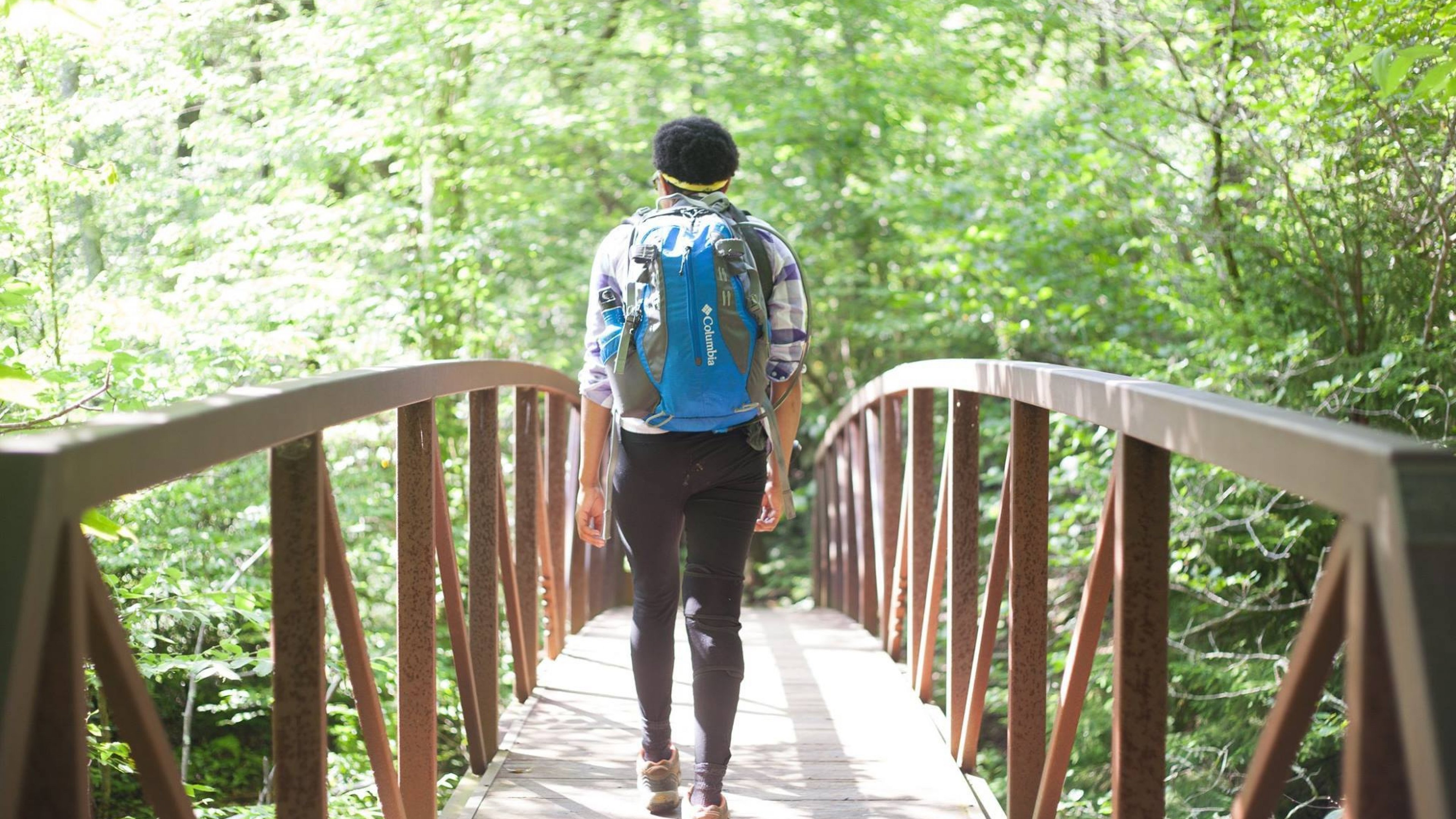 Brittany walks over a wooden bridge among the green of the trees, carrying a Columbia backpack.