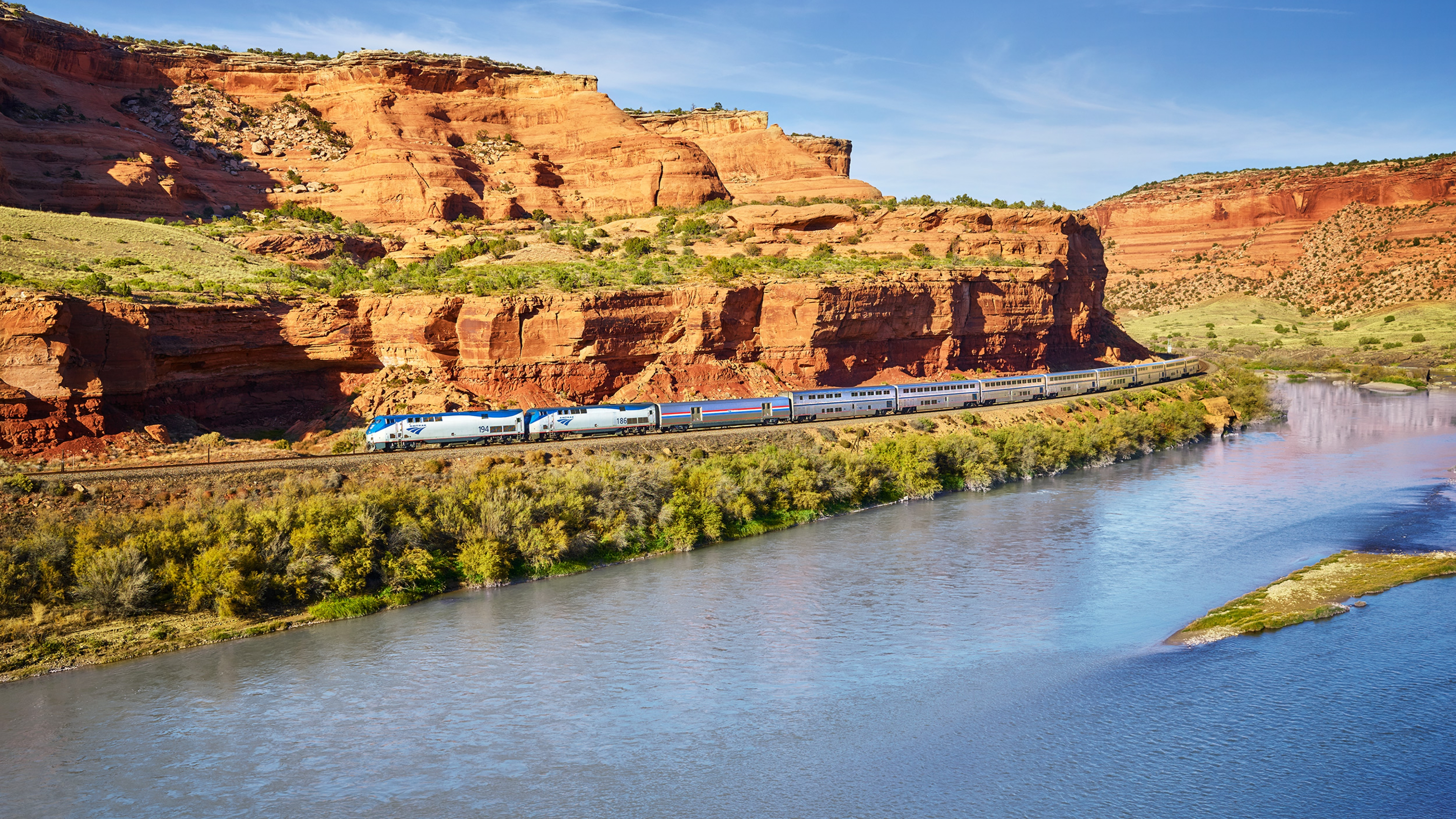 Train chugging alongside a river and red canyon walls.