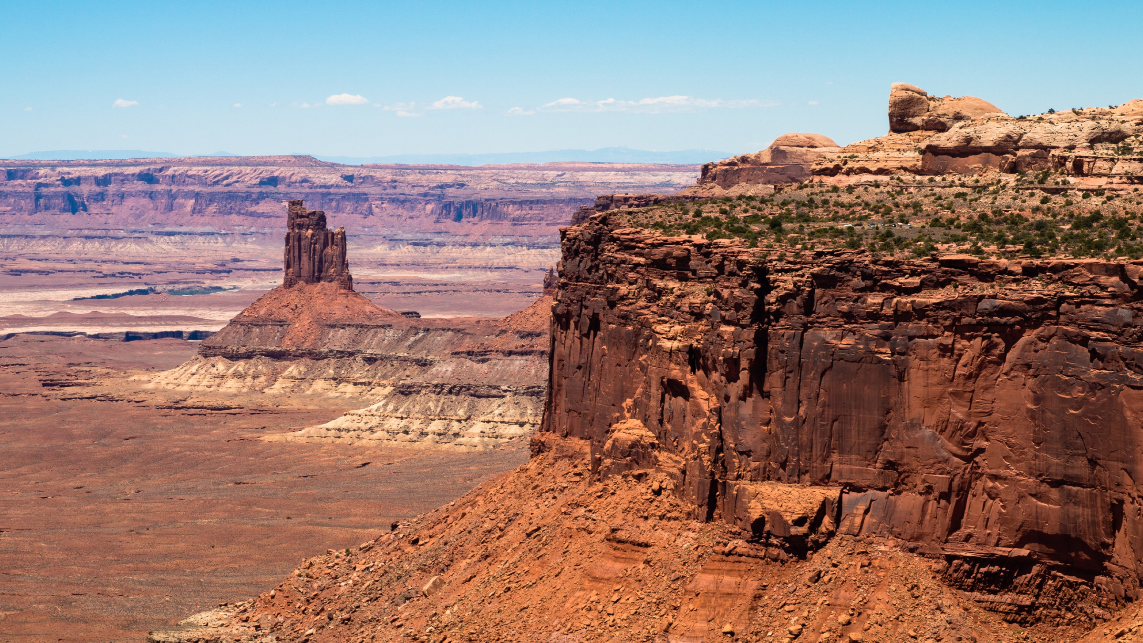 Tall cliffs and rock towers rise above the floor of the desert