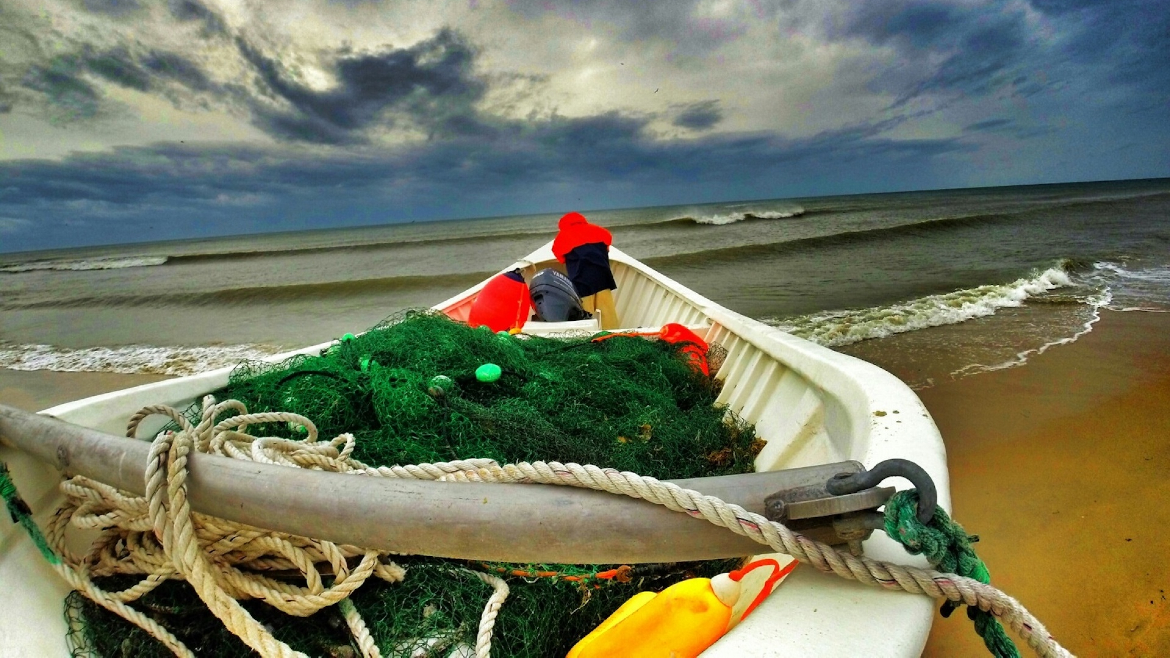 A fishing boat filled with equipment lies on the stormy shore at Cape Hatteras National Seashore.