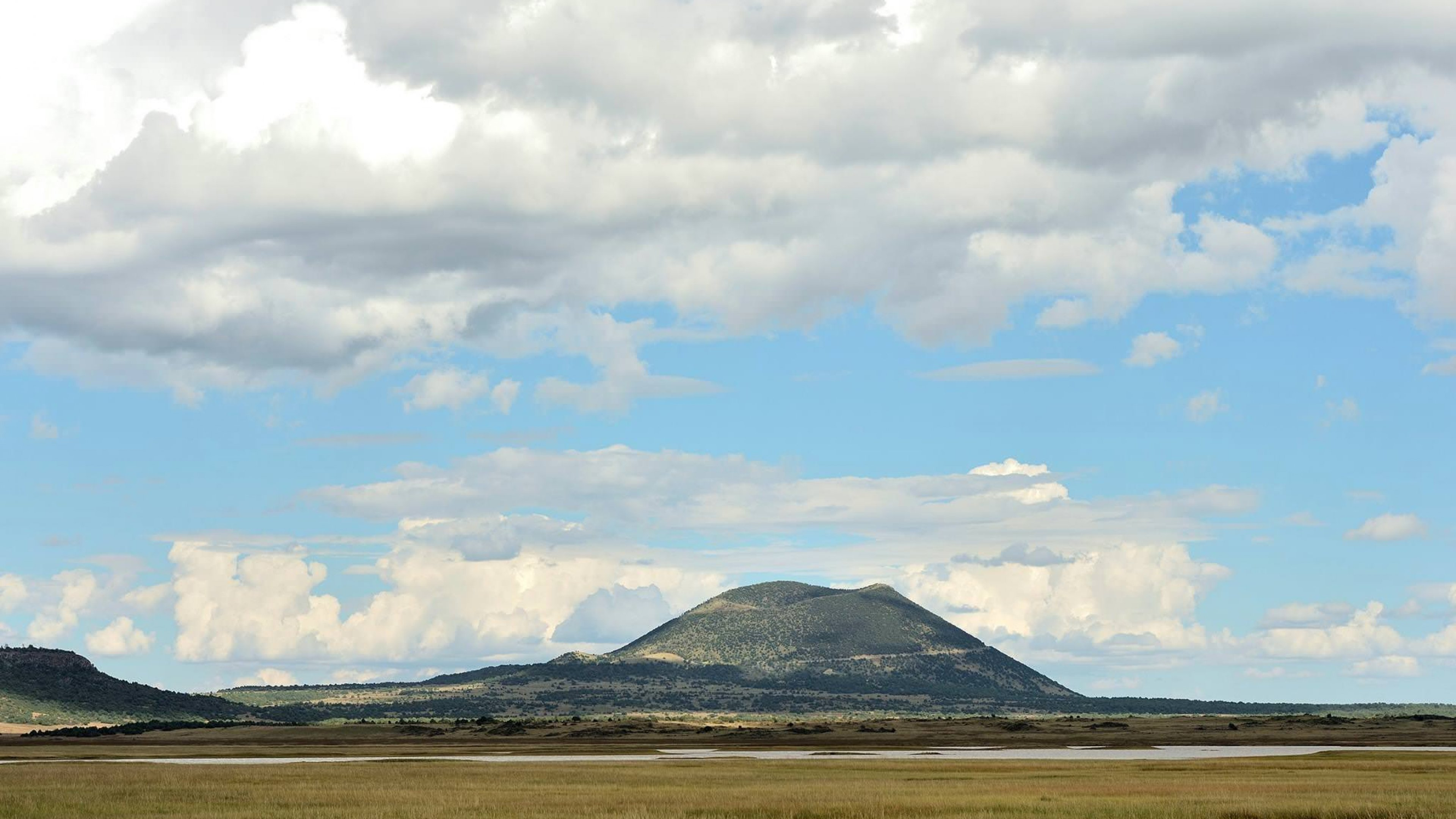 White clouds in a bright blue sky over Capulin Volcano National Monument in the horizon