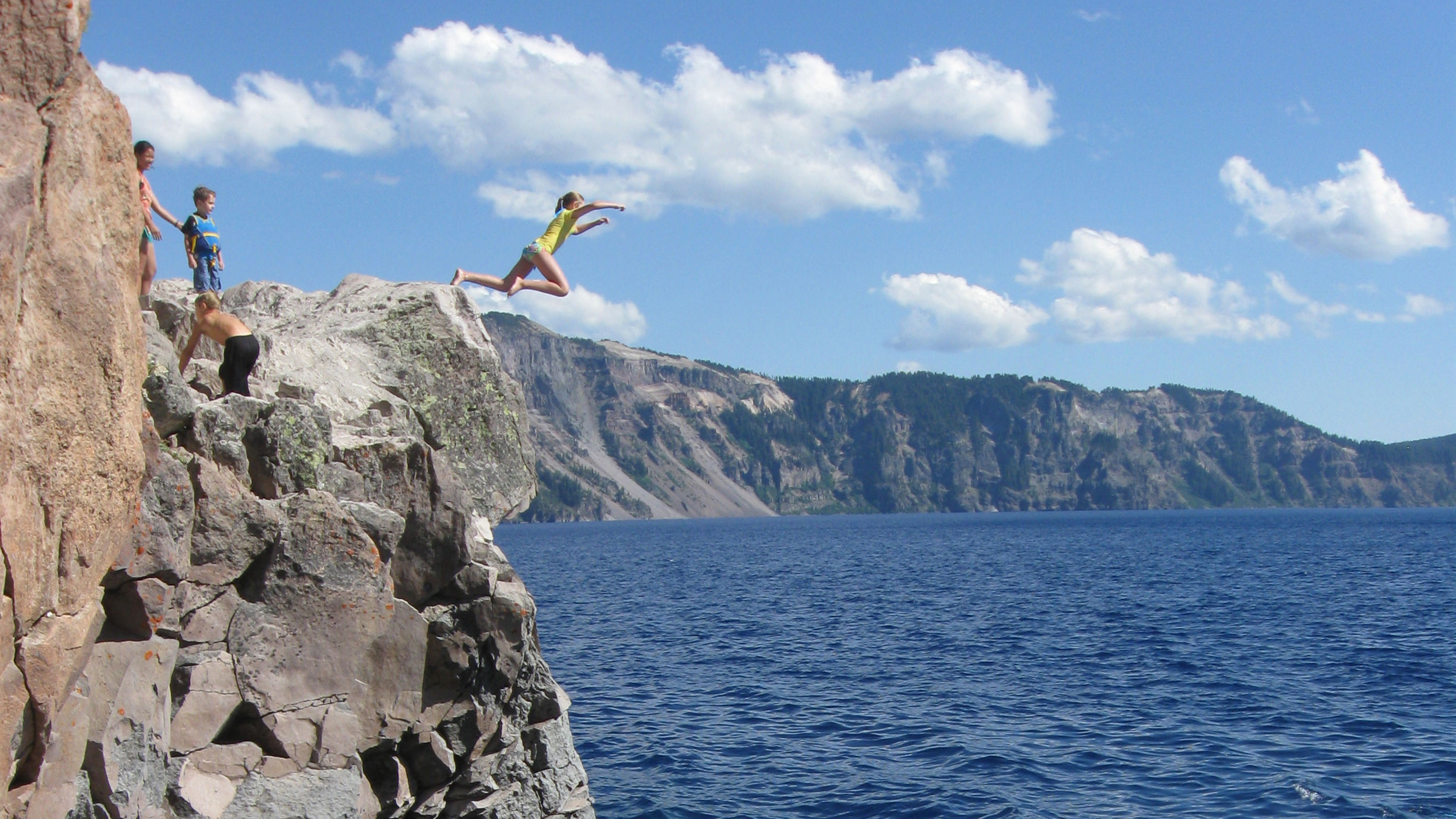 A girl jumping off a cliff into the lake at Crater Lake National Park