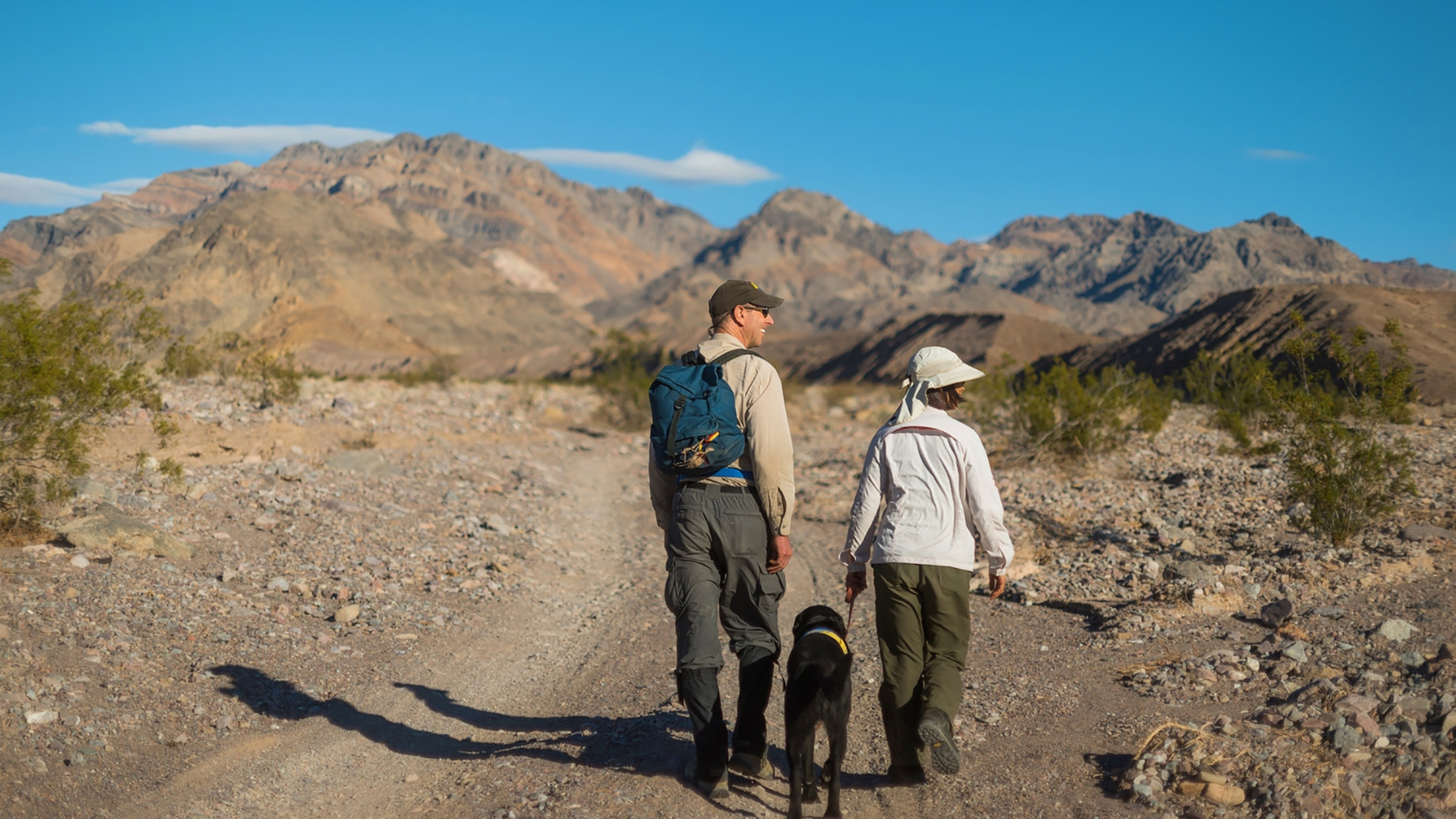 A man and woman with a black Labrador Retriever on an unpaved road, with mountains and a blue sky in the distance.