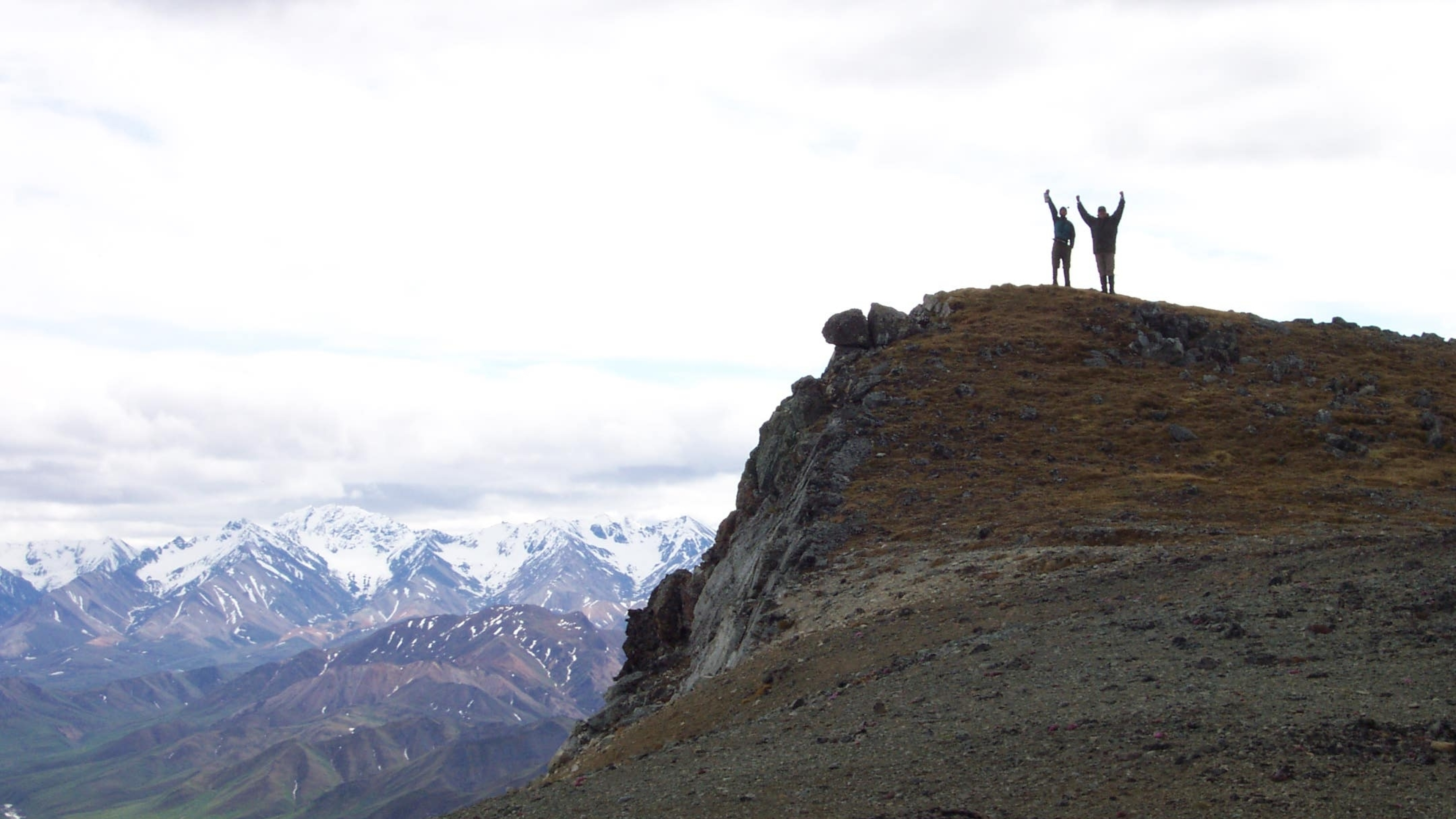 Hikers raise their arms to celebrate hiking up a steep slope