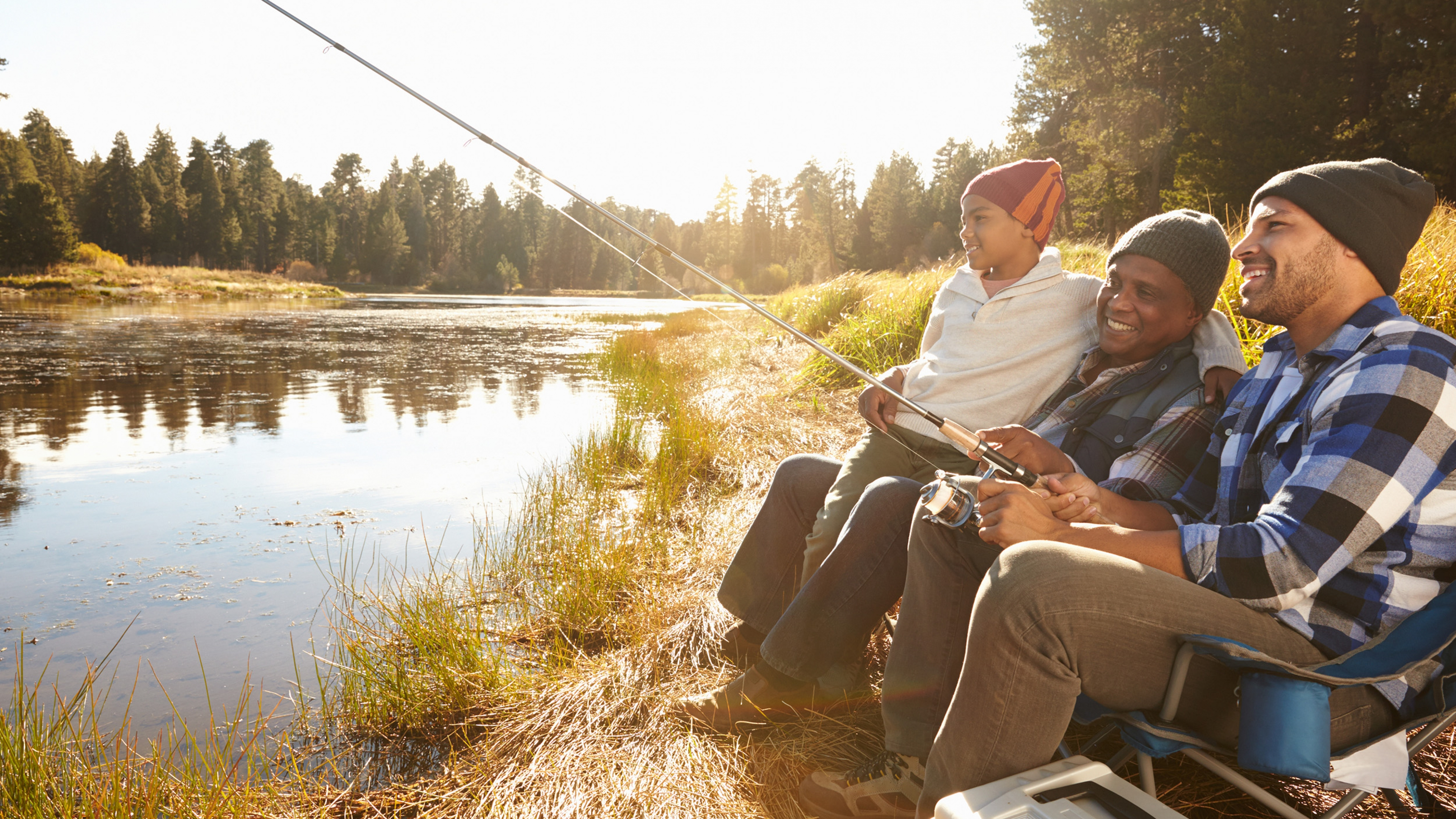 Three generations of family sit beside a lake, fishing and smiling.