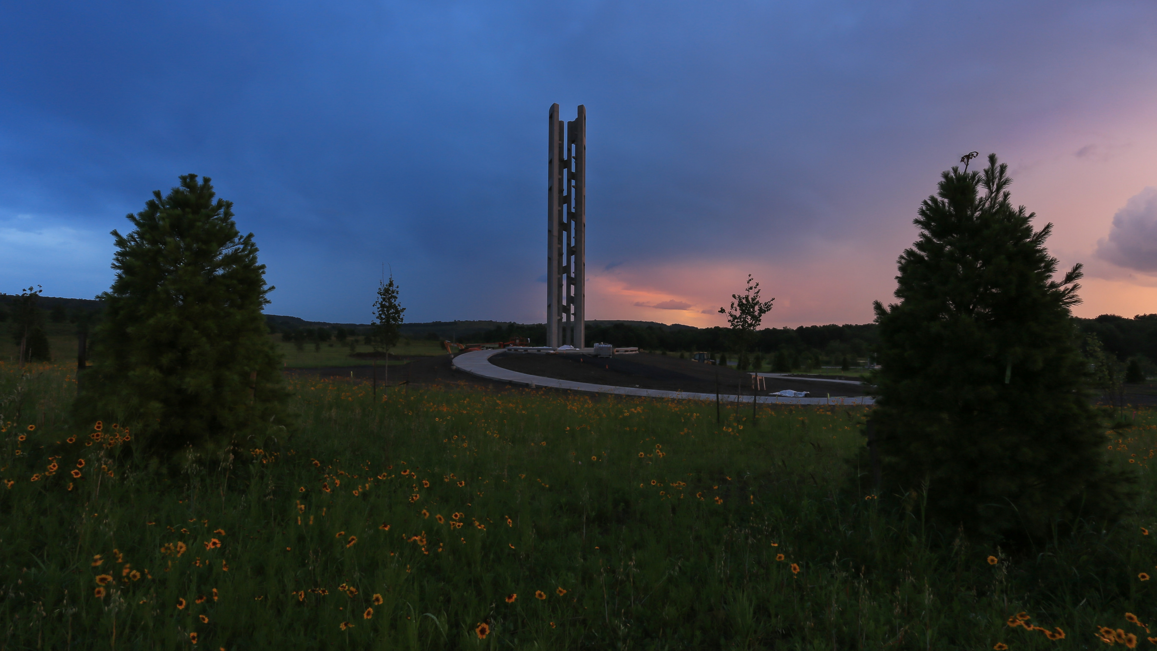 The gray, window-filled Tower of Voices is set between two pine trees against a sunset with deep blue, light purple, and pink clouds