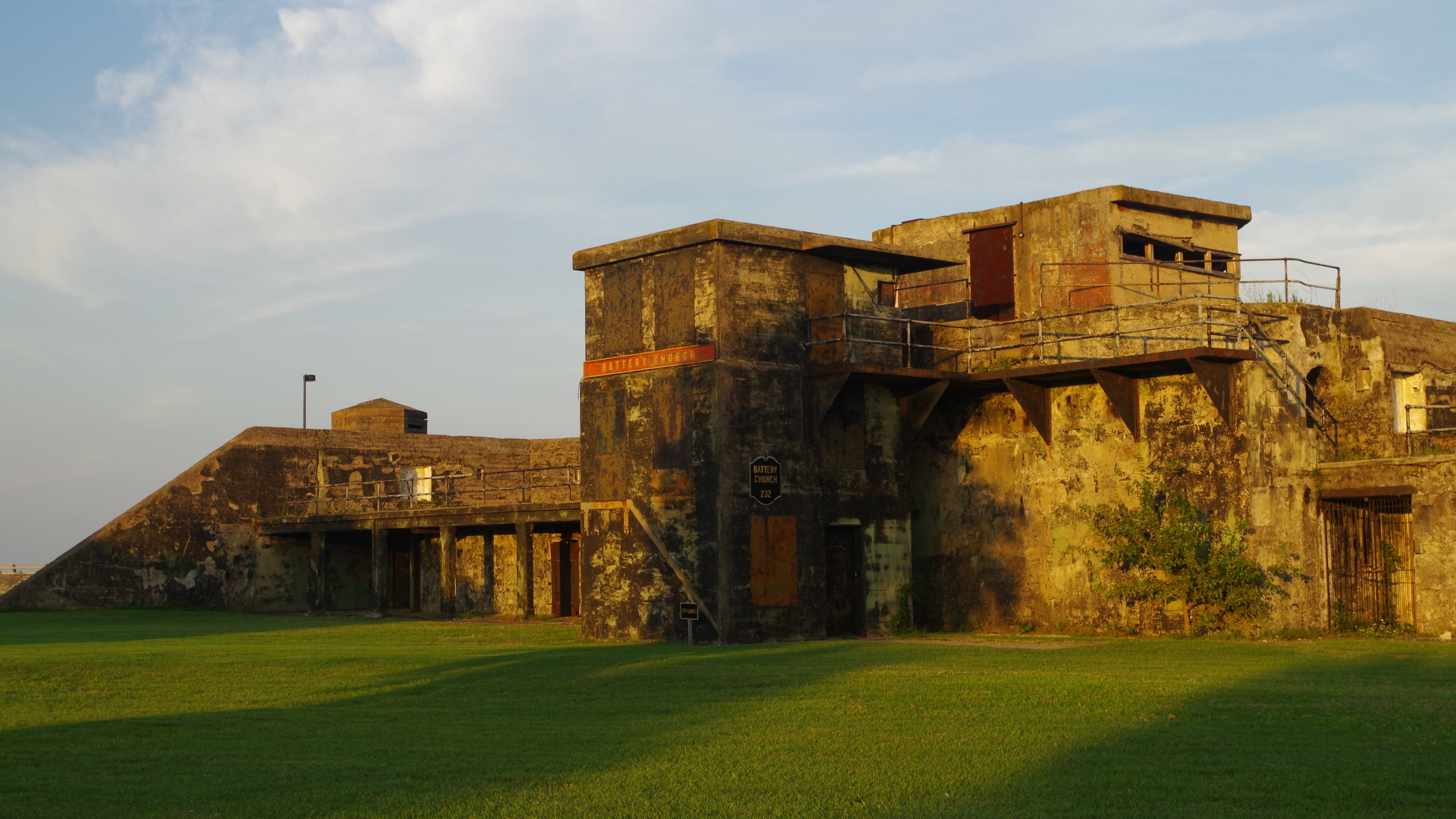 Battery Church in the golden sunset light in front of green grass at Fort Monroe National Monument
