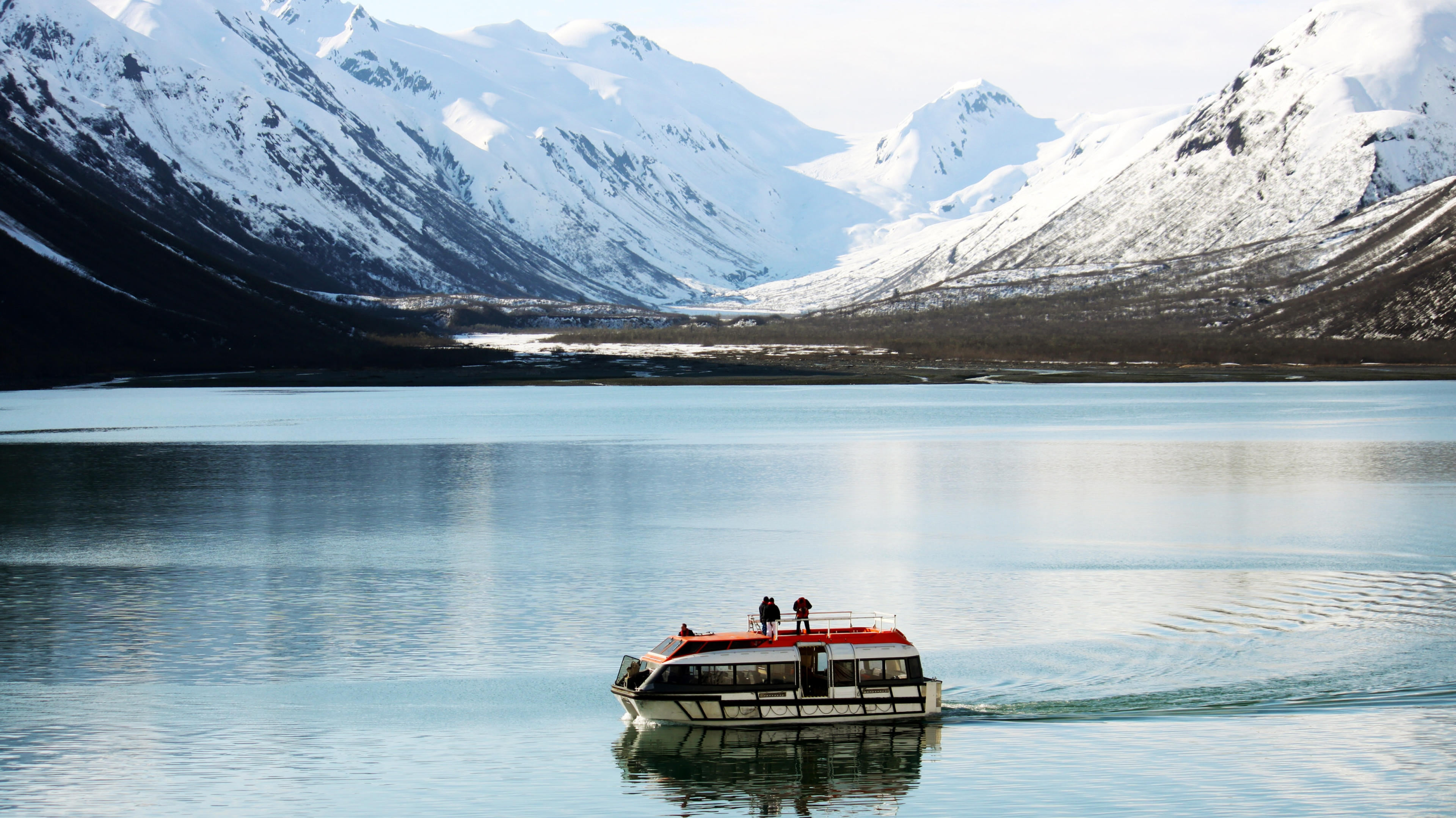 Tour boat in the bay in front of snow and glacier-covered mountains at Glacier Bay National Park & Preserve