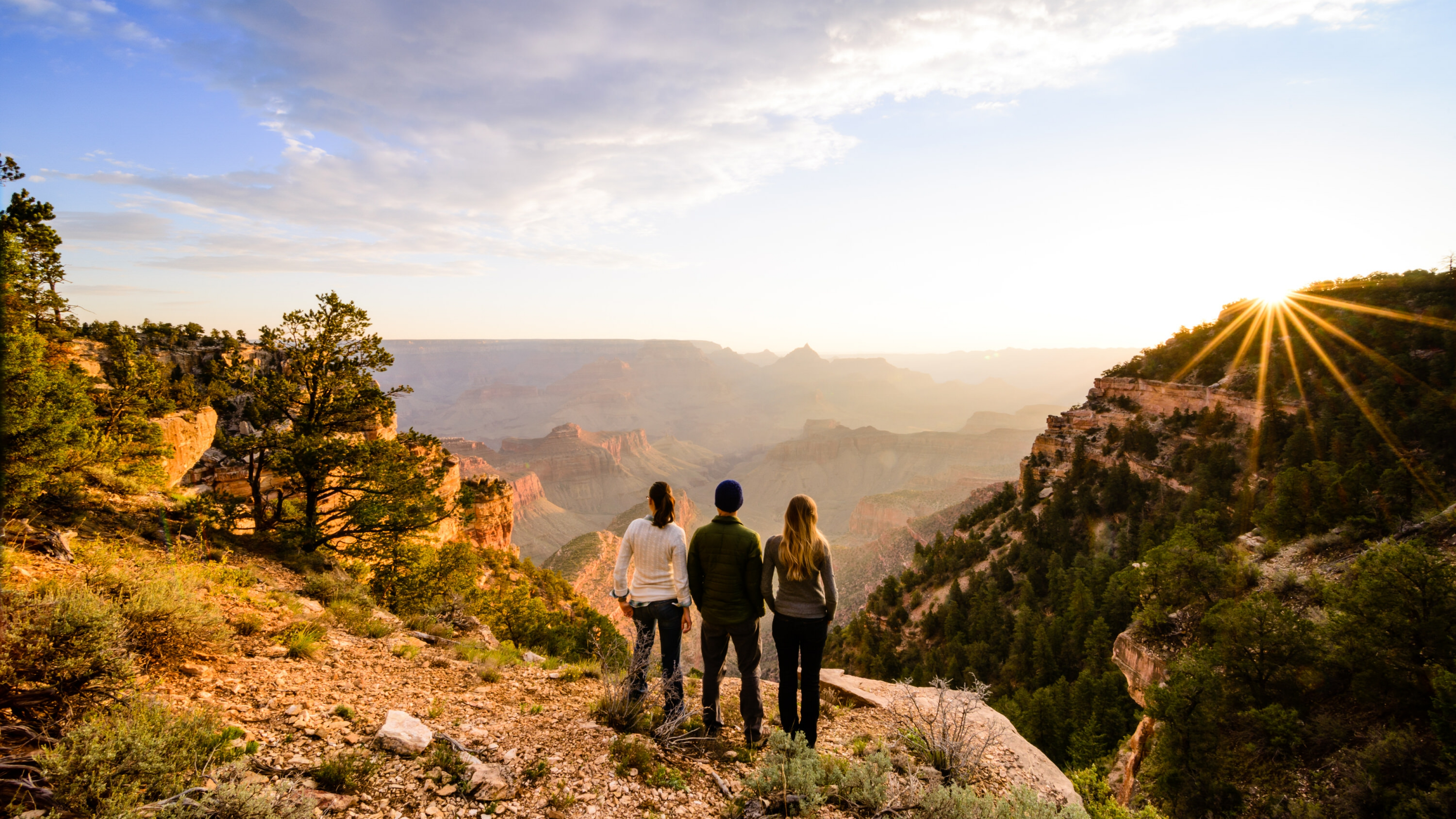Three people standing at the edge of a cliff at Grand Canyon National Park